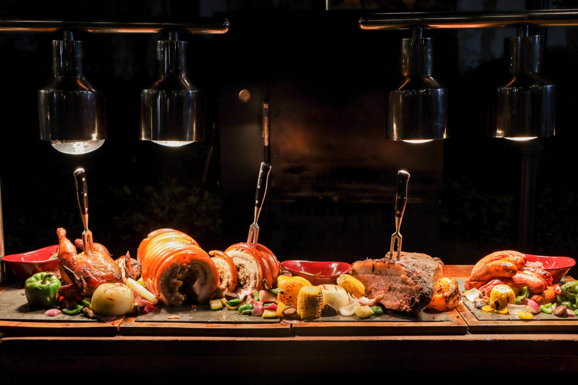 Succulent roast chicken, pork belly, and beef beautifully plated with an array of vegetables at Sofitel