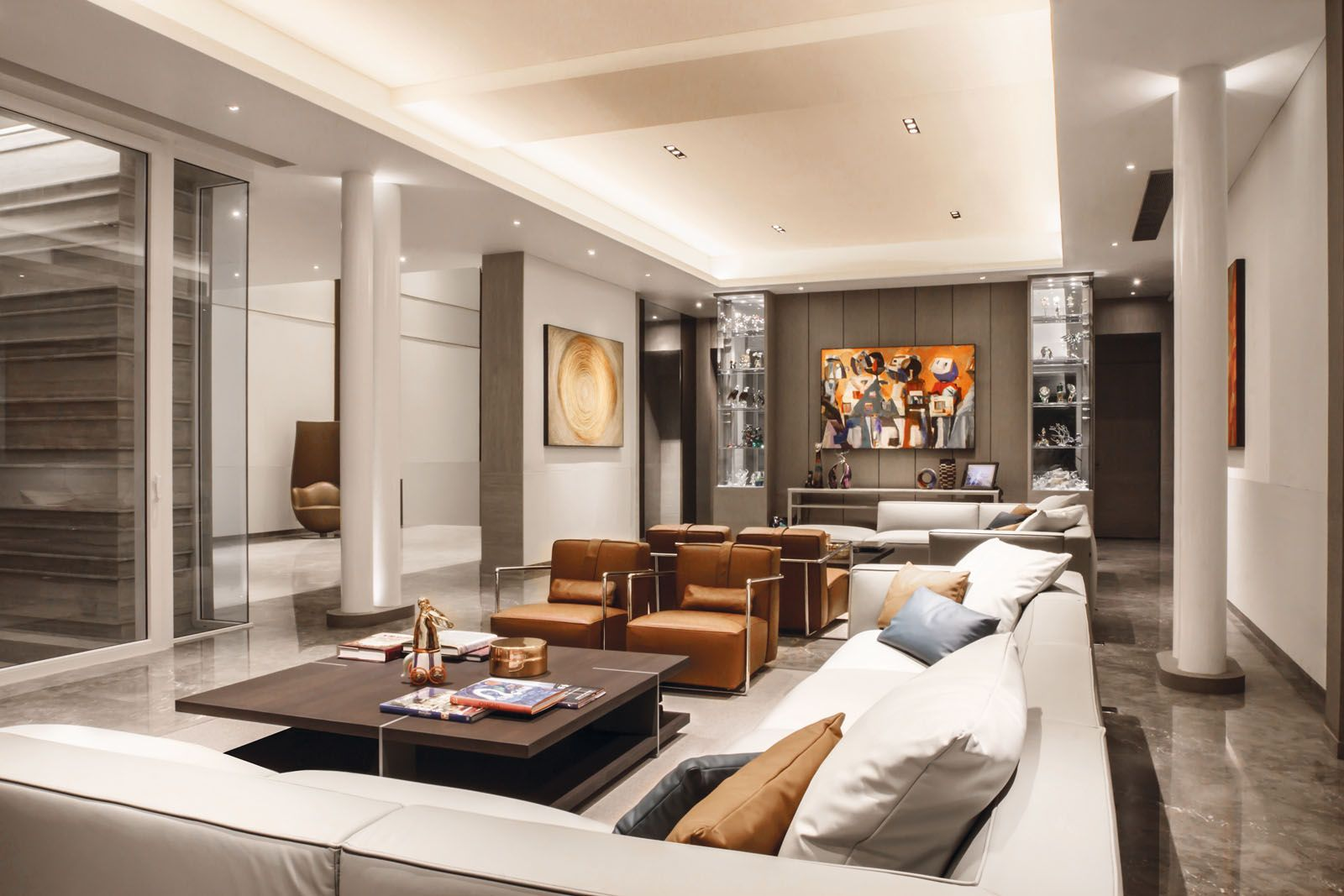 The living area features Poliform coffee tables and sectional sofas, and armchairs from Flexform