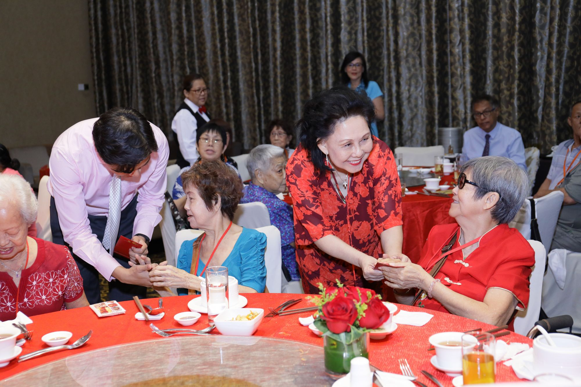 Cecilia Kwek and Kwek Eik Sheng (in  pink) present the old folks from Henderson Home with red packets at the luncheon.