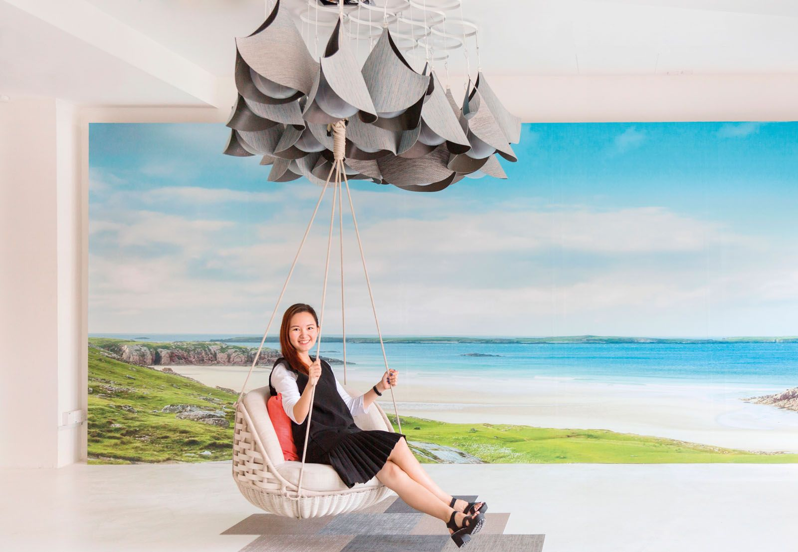 Fraction Design Studio founder and designer Celine Ng with Cloud 9, a collaboration with Bolon and Xtra. The installation is composed of cloud forms, painting a surreal experience of swinging high in the sky