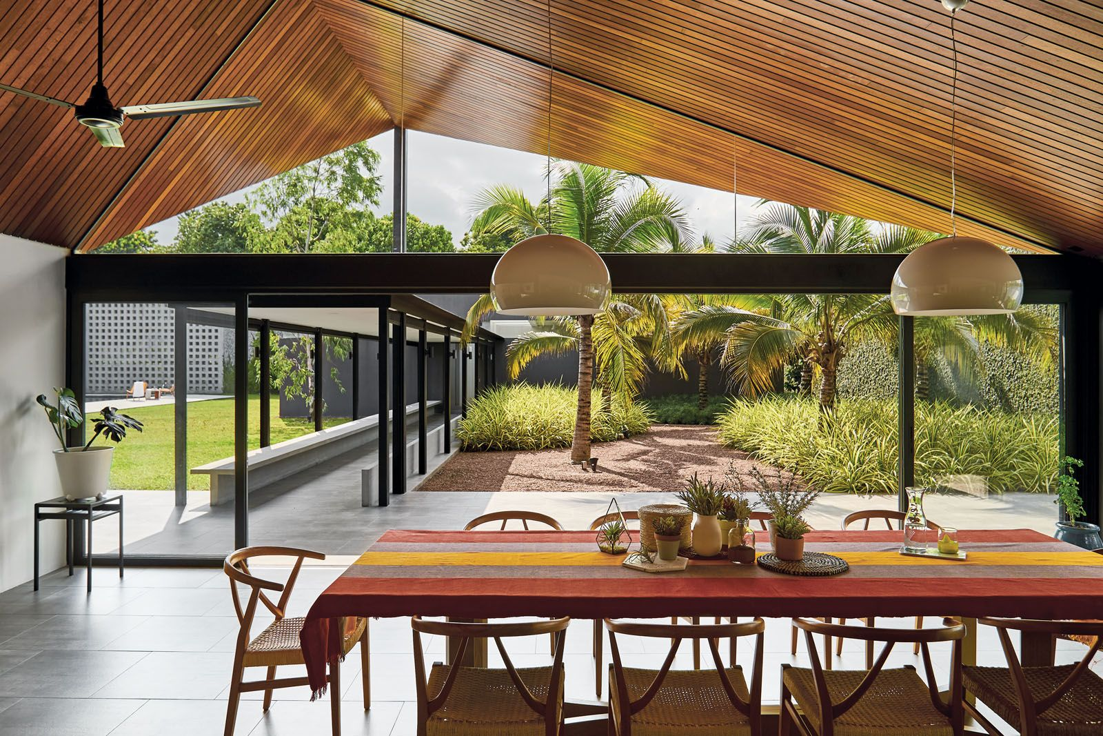 The dining area features a row of Kartell FL/Y pendant lights that float above the wooden furnishings