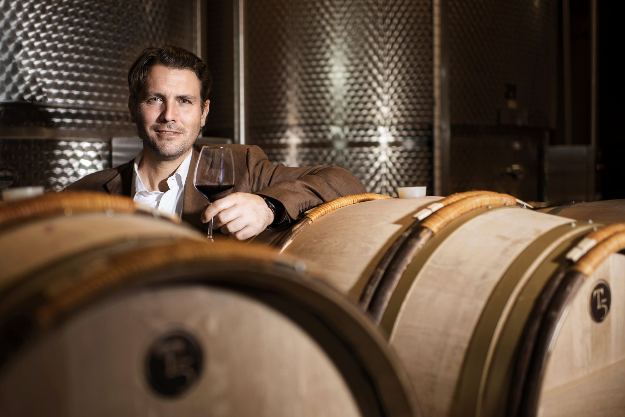 Salvatore Ferragamo, CEO of Il Borro, posing in between handmade wine barrels.
