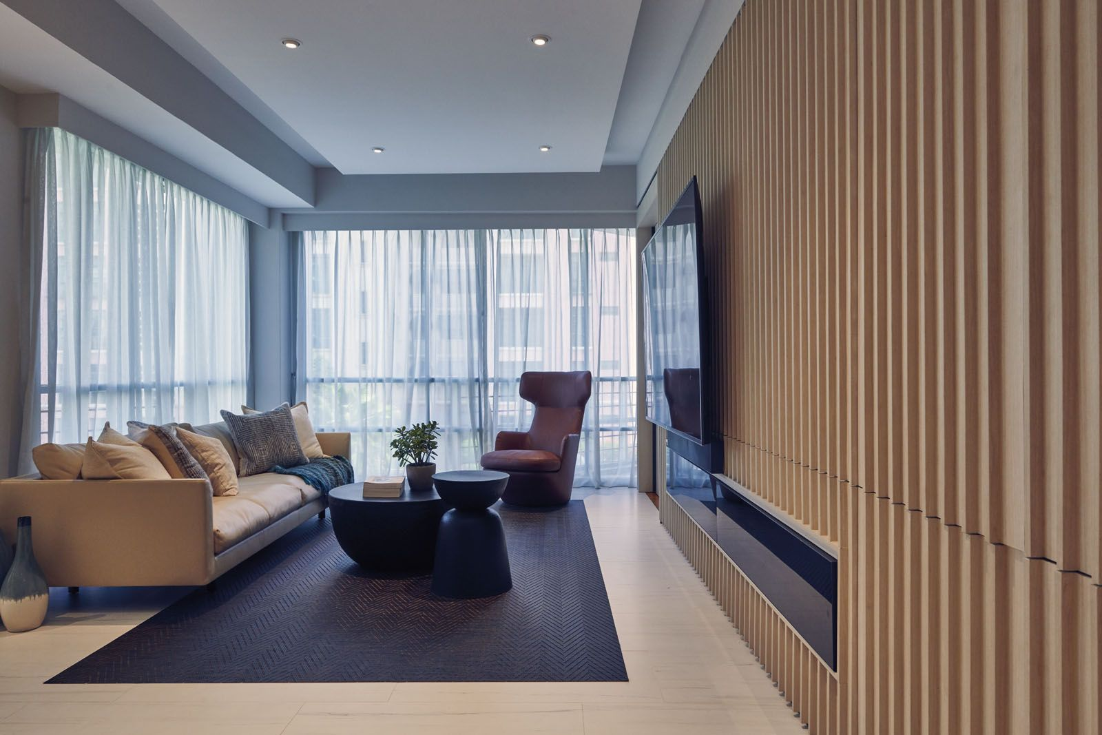 The wooden panelling functions as a sliding door while housing storage and the built-in TV console