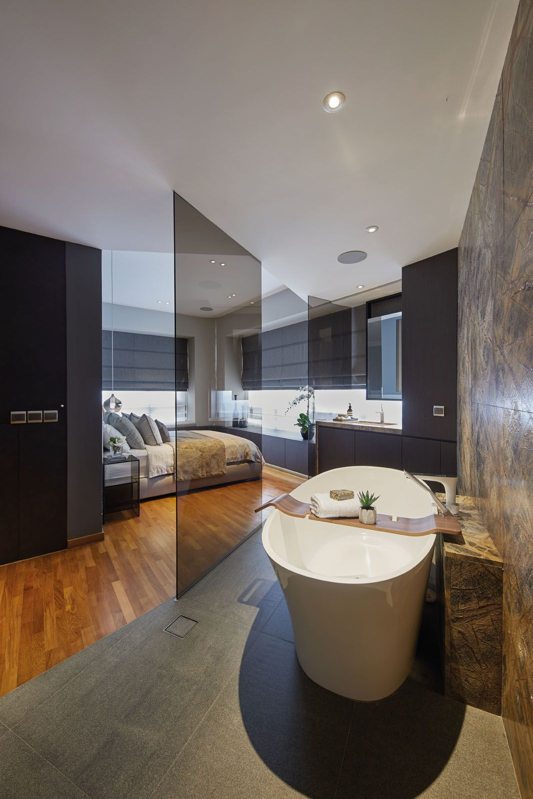Tinted glass panels separate the bedroom area from the bathroom