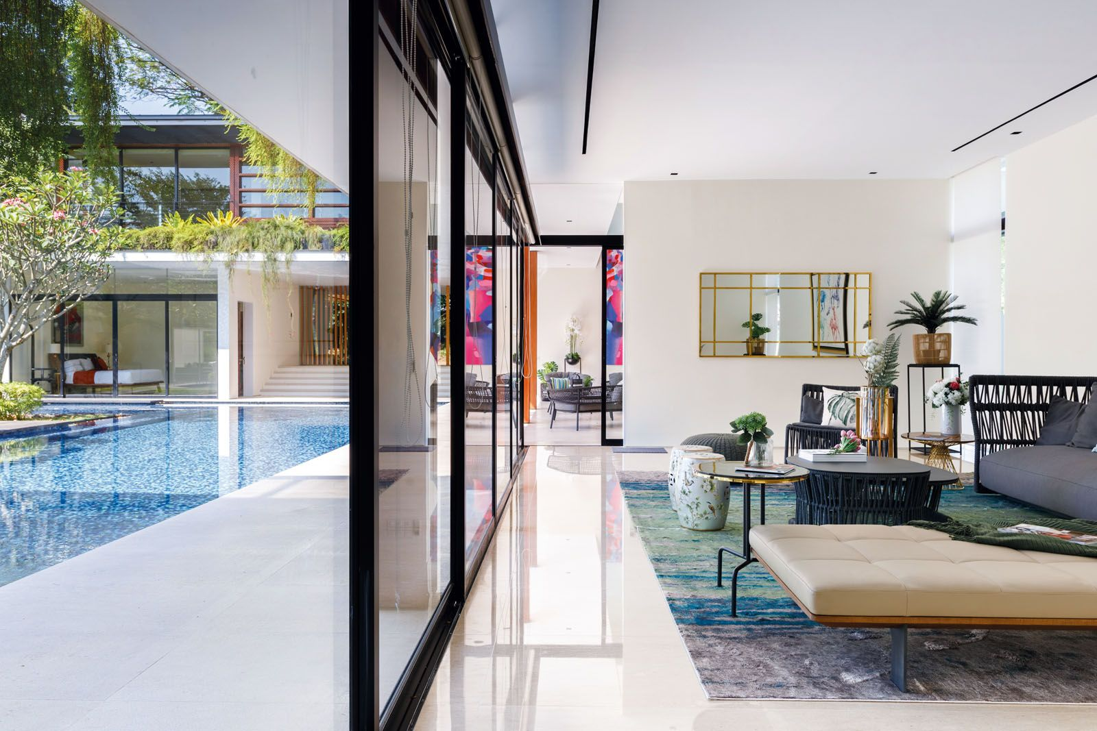 Strategically placed plants and the clever use of emerald tones in the living room draw the eye to the pool and the lush courtyard