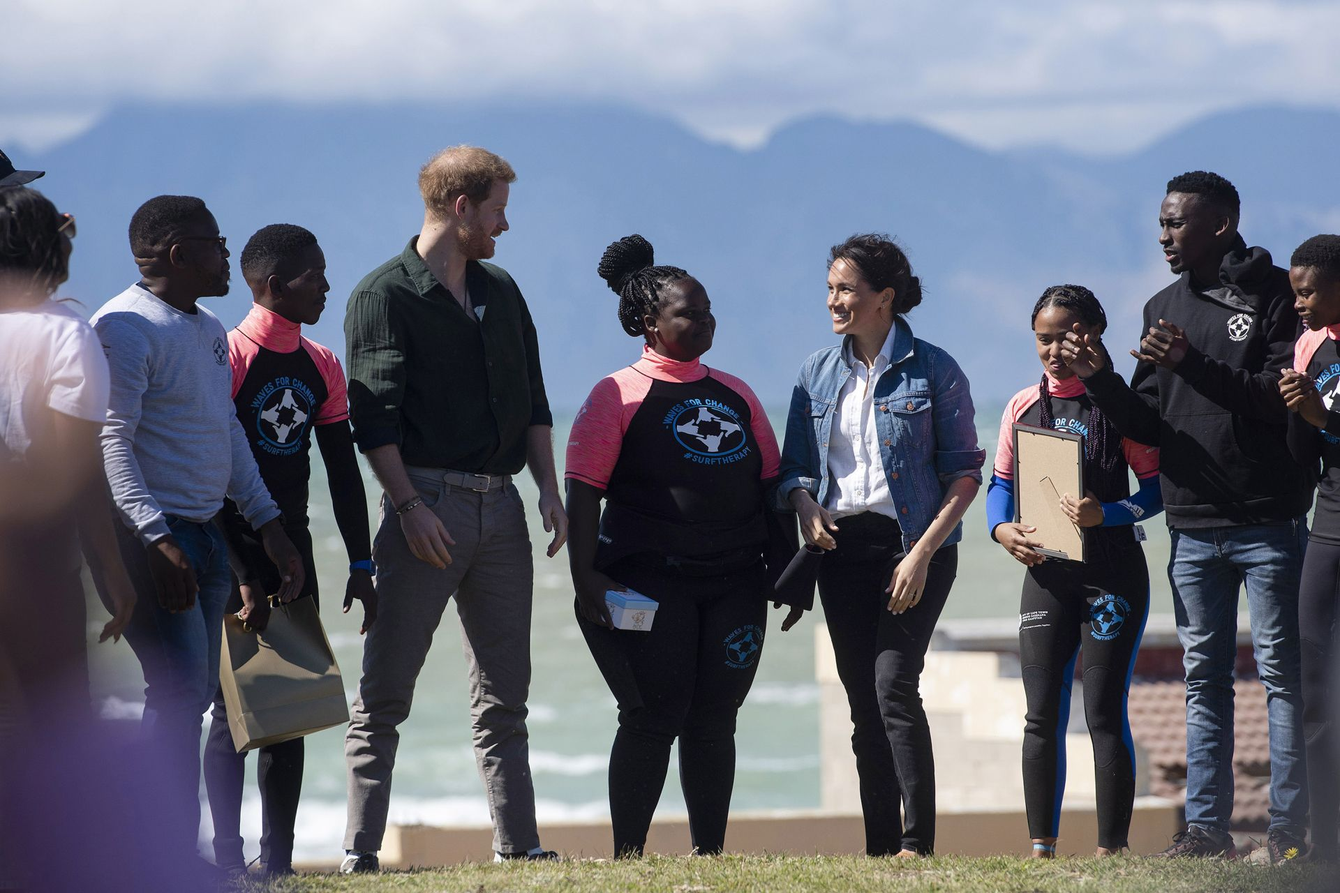 "Prince Harry (4thL), Duke of Sussex and Meghan (4thR), Duchess of Sussex, meet members of ""Waves For Change"" NGO at Monwabisi Beach outside of Cape Town on September 24, 2019. - ""Waves For Change"" NGO fuses surfing with child-friendly mind and body therapy to provide mental health services to vulnerable young people living in challenging communities. (Photo by DAVID HARRISON / AFP)"