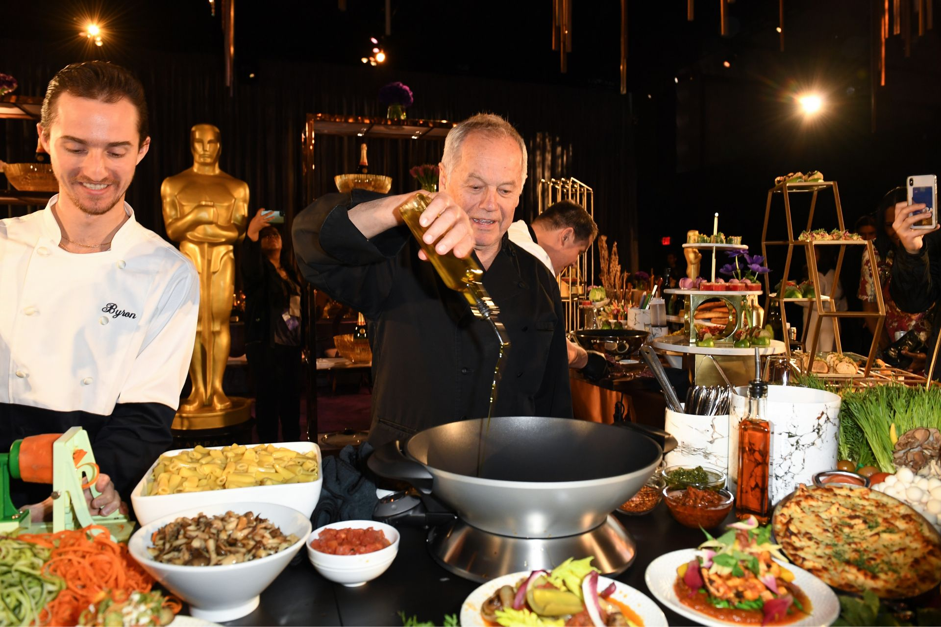 US-Austrian chef Wolfgang Puck (C) and son Byron Puck (L) prepare a dish during the 92nd Annual Academy Awards Governors Ball press preview at The Ray Dolby Ballroom at Hollywood & Highland Center, in Hollywood, California, on January 31, 2020. (Photo by VALERIE MACON / AFP)