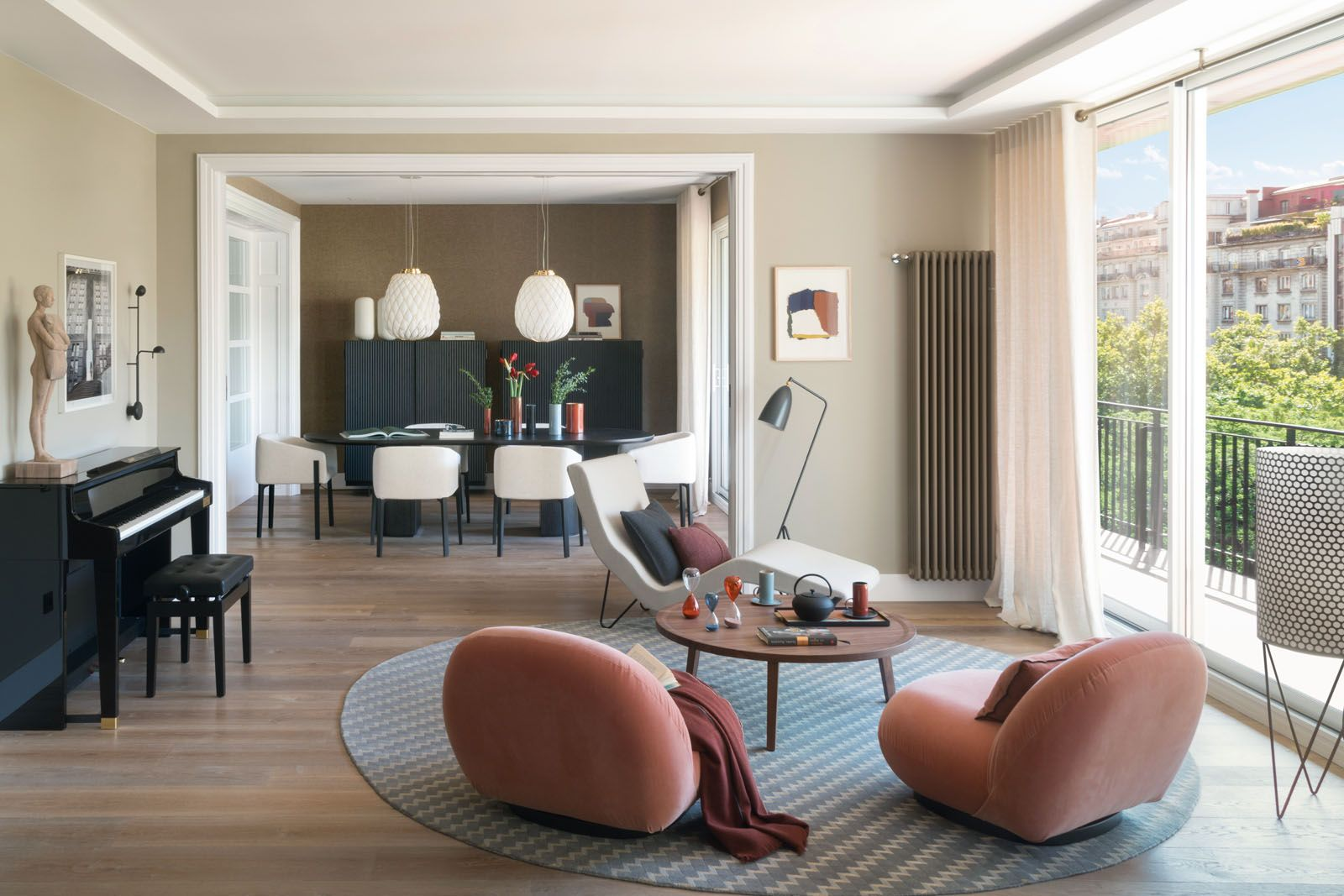 The reading lounge features floor lamps, armchairs and an ottoman from Gubi, a BSB Alfombras rug and a Gervasoni side table; abstract art and sculptures from Galería Víctor Lope Arte Contemporáneo and Galeria Miquel Alzueta complement the apartment's understated interior scheme