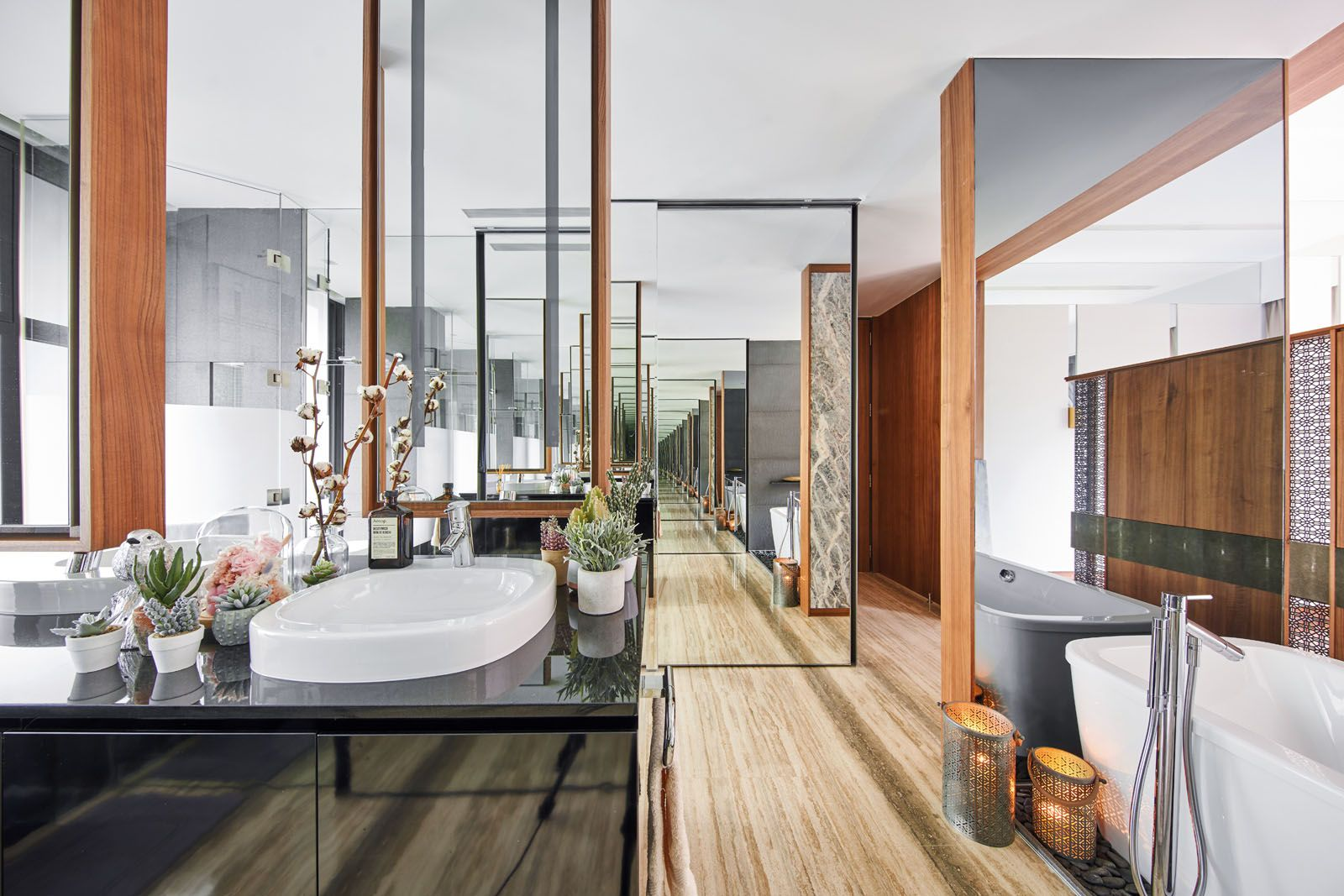 The clever use of glass in the master bathroom creates the illusion of an endless hallway;