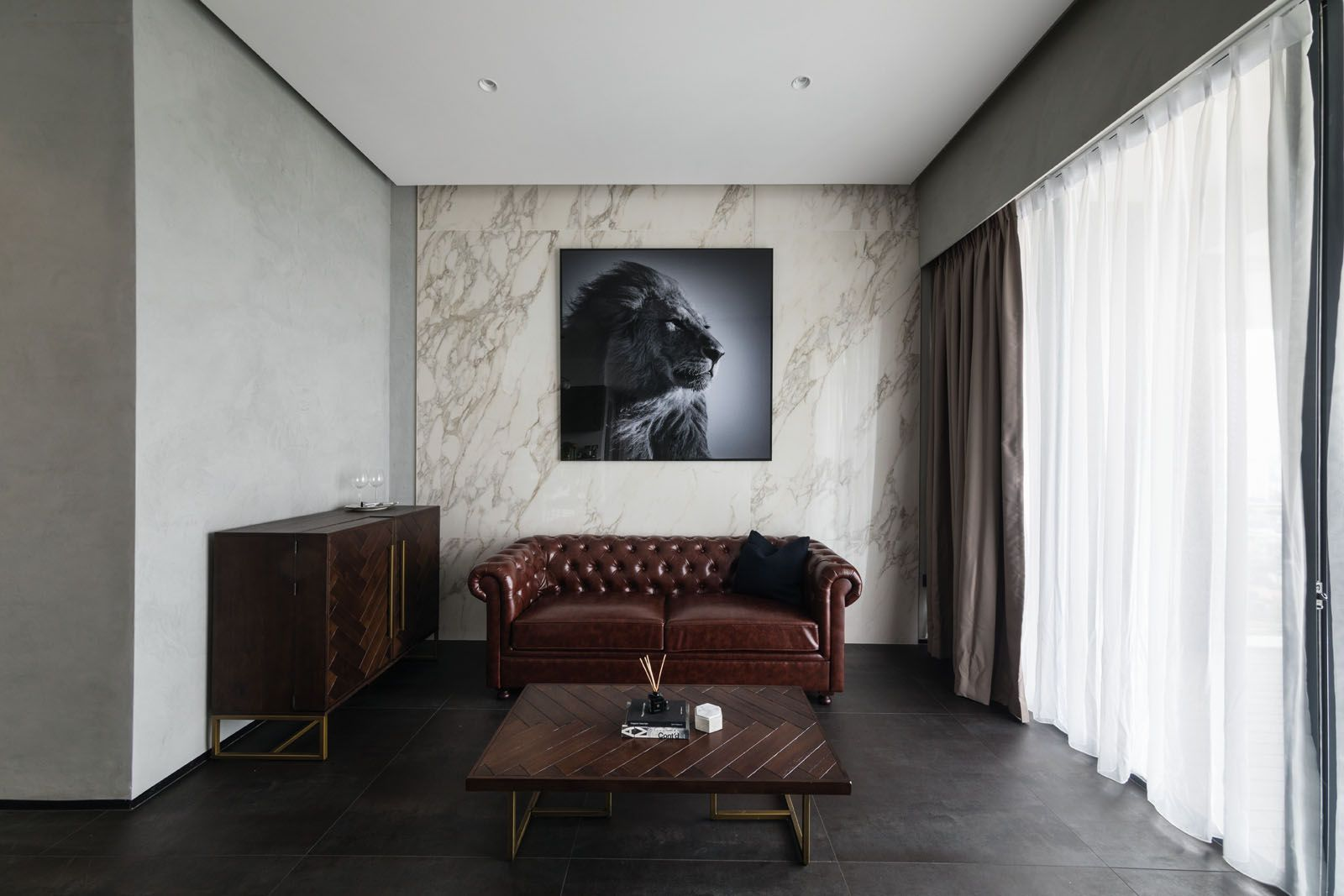 The stucco used for the walls in the living room serves as a neutral background that provides a stylish contrast when paired with leather, timber and marble