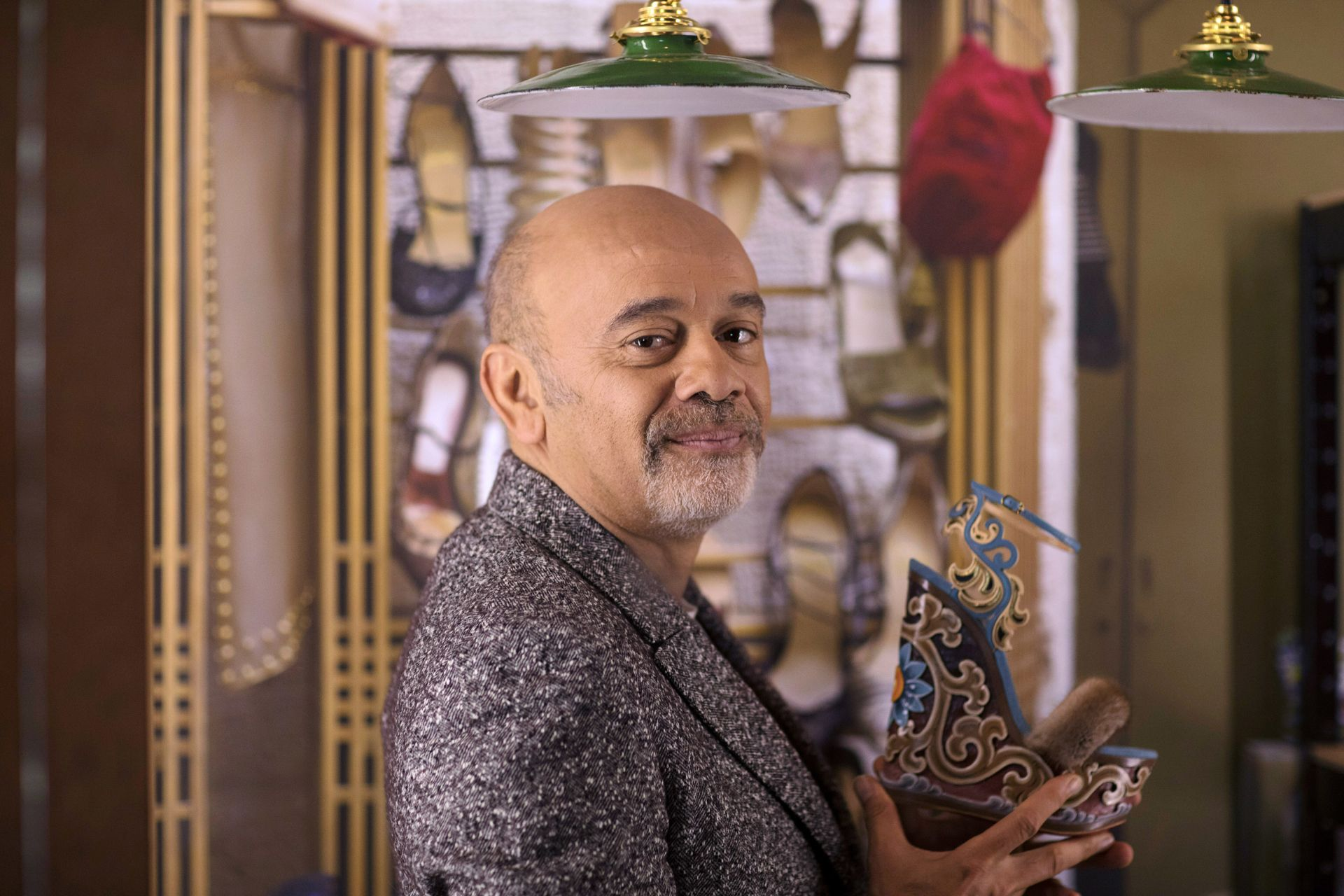 "French shoe designer Christian Louboutin poses with one of his creations during a photo session at the Palais de la Porte Doree in Paris a few days before the opening of his exhibition ""L'Exhibition-iste (The Exhibition-ist). - ""L'Exhibition-iste (The Exhibition-ist) exhibition runs from February 26 to July 26, 2020. (Photo by Tonje THORESEN / AFP)"