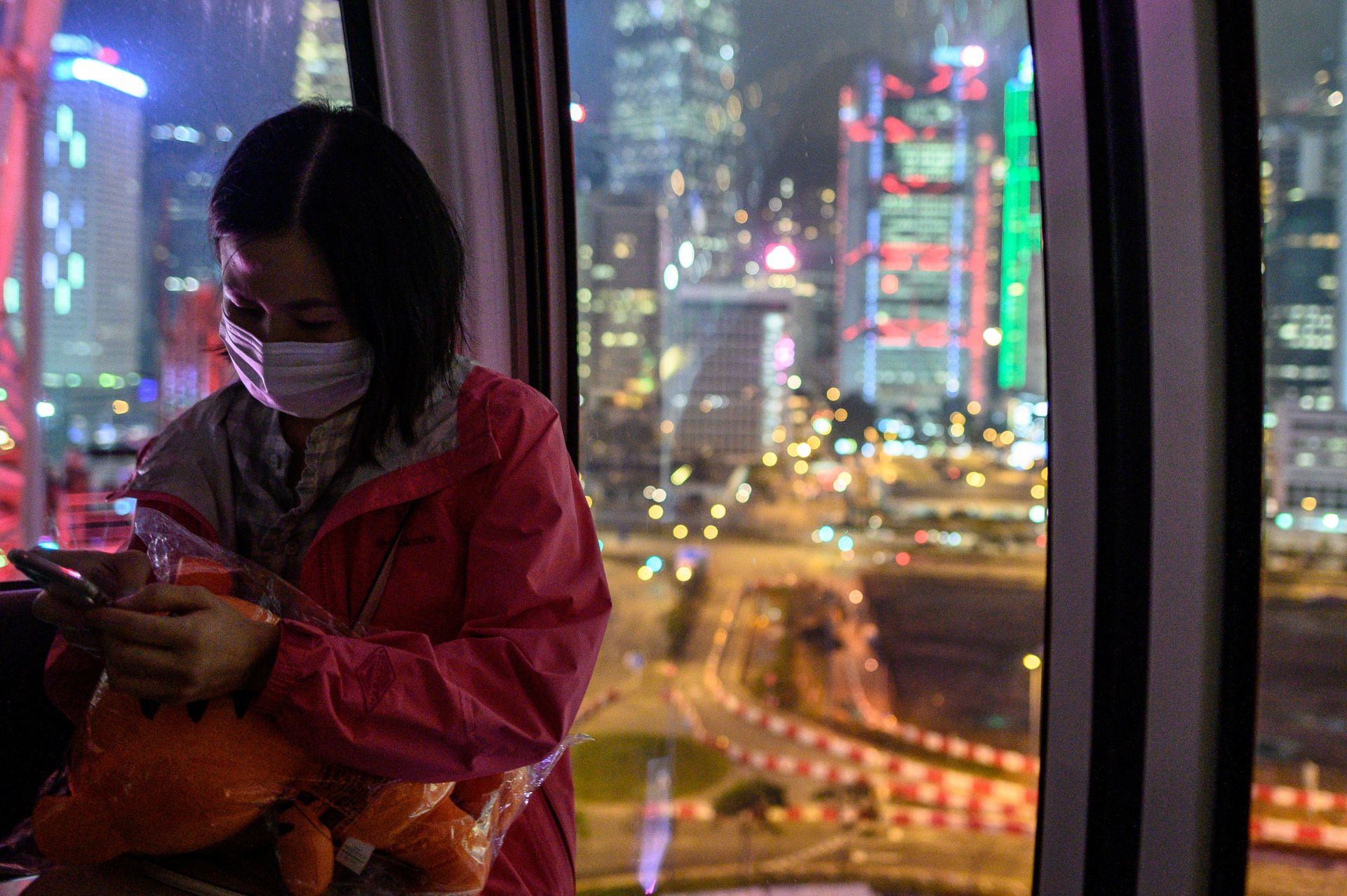 A woman wears a face mask as a preventative measure against the COVID-19 coronavirus, as she sits inside a cabin of the ferris wheel in Central district of Hong Kong on February 14, 2020. - The death toll from China's virus epidemic neared 1,400 on Friday with six medical workers among the victims, underscoring the country's struggle to contain a deepening health crisis. (Photo by Philip FONG / AFP)