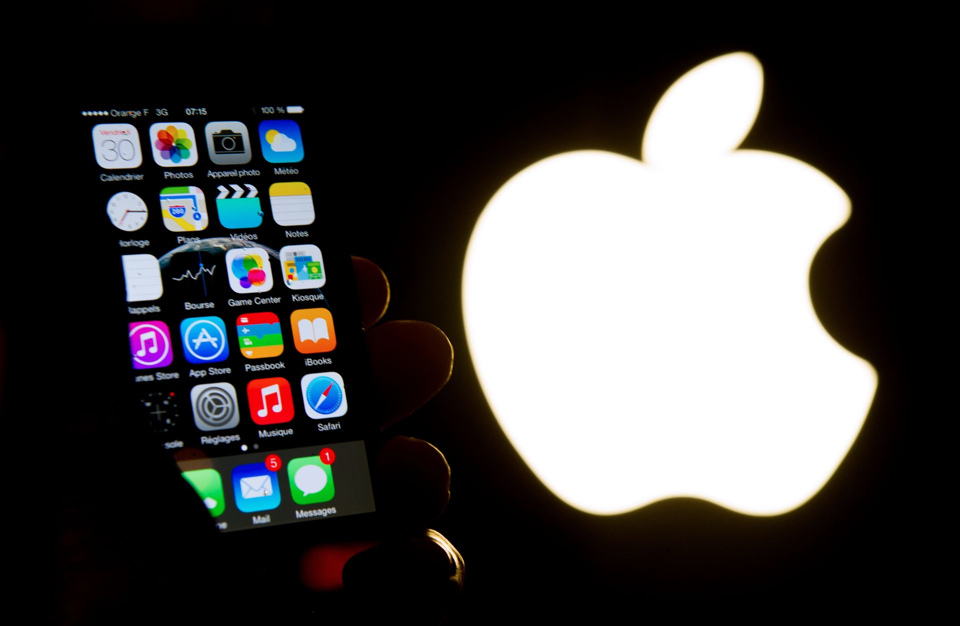 An illustration of an iPhone held up in front of the Apple Inc. logo taken of January 30, 2015 in Lille.  AFP PHOTO / PHILIPPE HUGUEN / AFP PHOTO / PHILIPPE HUGUEN