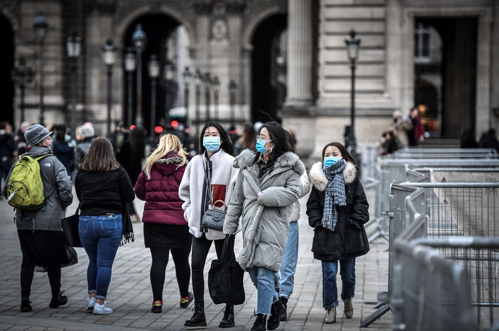 Tourists wearing a protective face mask amid fears of the spread of the covid-19 coronavirus at the Pyramide du louvre area in Paris. (Image: Stephane De Sakutin/AFP)