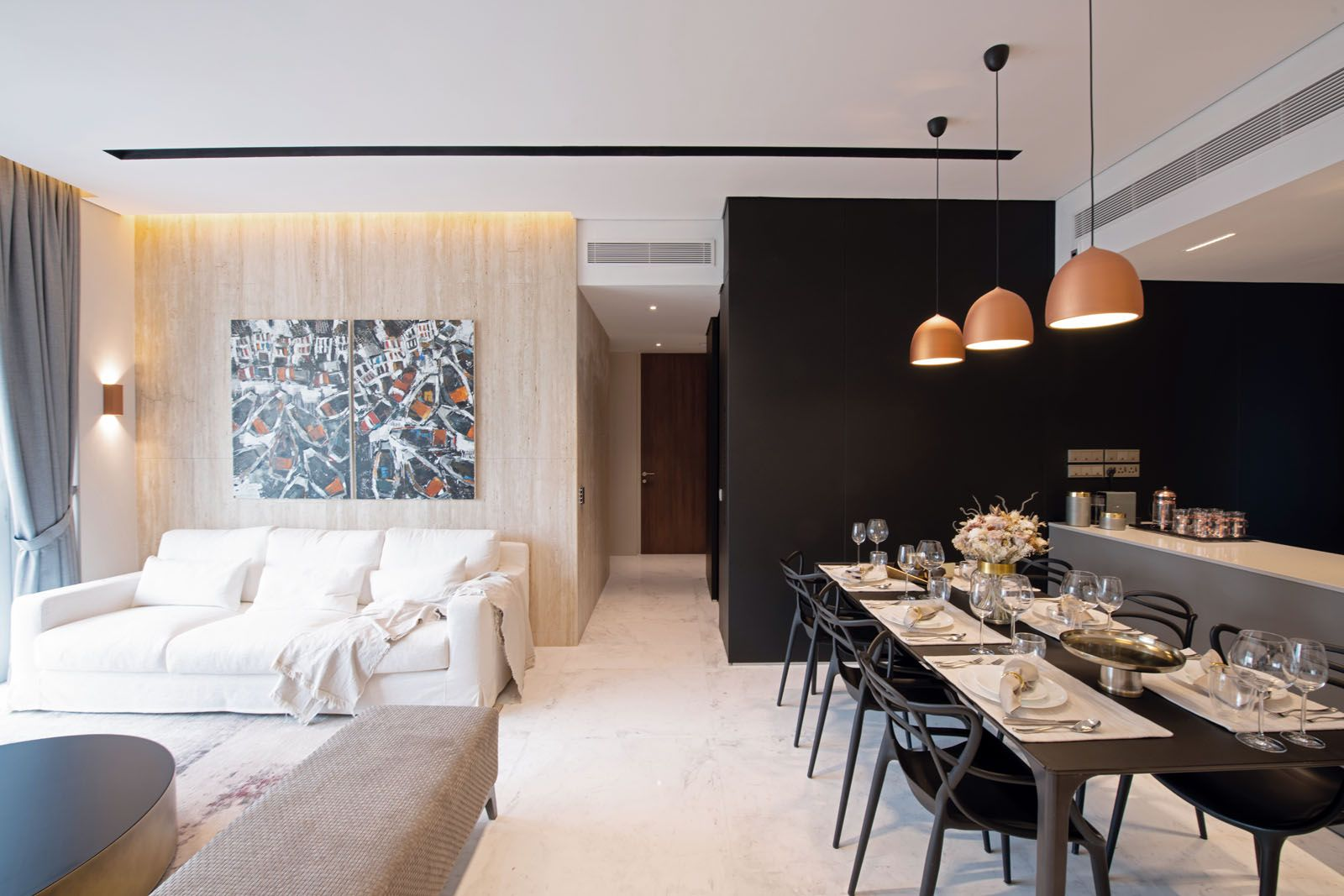 The earthy tones of the travertine wall are juxtaposed against the sleek black laminate wall that wraps around the kitchen, dining area and hallway