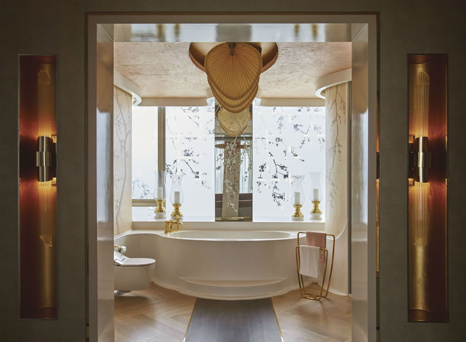A bathroom crafted by Design Intervention features ample use of gold accents and ample use of ambient lighting