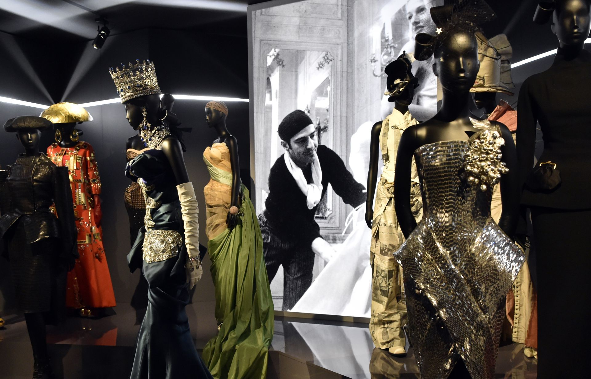 Dresses by British fashion designer John Galliano (whose picture is seen behind) are pictured during the Dior exhibition that celebrates the seventieth anniversary of the Christian Dior fashion house on July 3, 2017 in Paris. - The exhibition at the Museum of Decorative Arts (Musee des Arts Decoratifs) is a retrospective presenting some 400 dresses, and runs through July 5, 2017 - January 7, 2018. (Photo by ALAIN JOCARD / AFP)