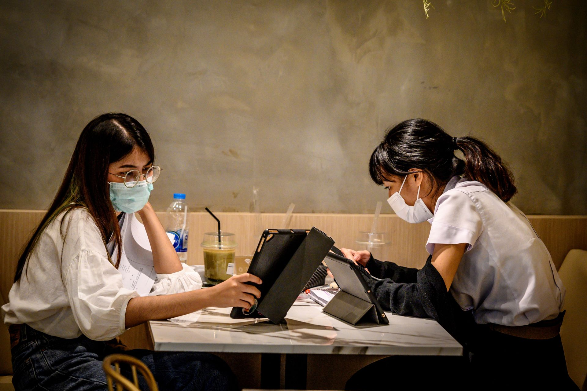 Students, wearing facemasks amid fears of the spread of the COVID-19 novel coronavirus, work in a coffee shop in Bangkok on March 3, 2020. - The world has entered uncharted territory in its battle against the deadly coronavirus, the UN health agency warned, as new infections dropped dramatically in China on March 3 but surged abroad with the US death toll rising to six. (Photo by Mladen ANTONOV / AFP)