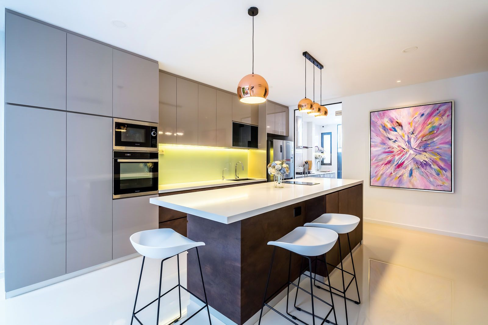An abstract artwork is the focal point of the kitchen