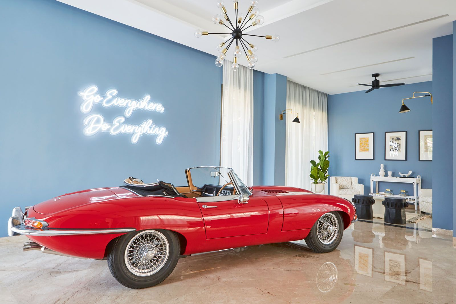 The red vintage sedan serves as the focal point of the living room