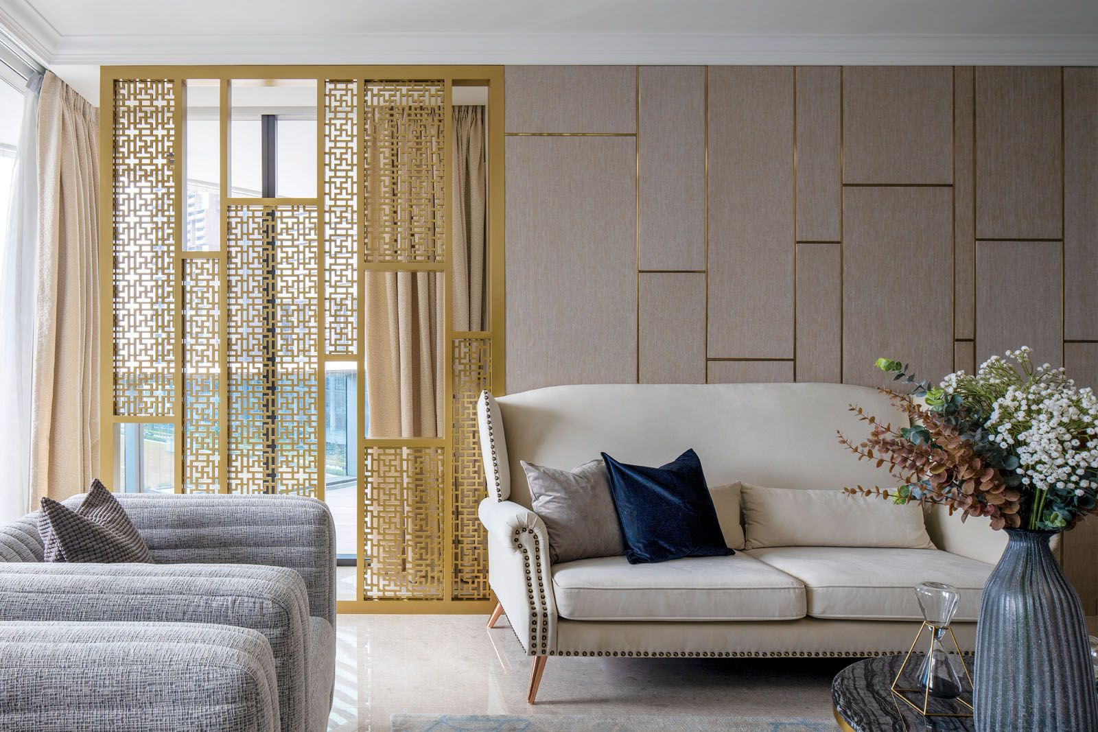 The gold lattice screen brings an opulent touch to the home while the neutral palette keeps the look elegant