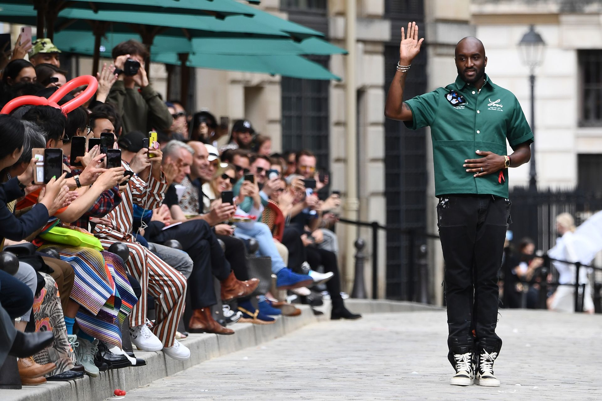 US fashion designer Virgil Abloh acknowledges the audience at the end of the presentation of Louis Vuitton's creation during the men's spring/summer 2020 fashion collection on June 20, 2019 in Paris. (Photo by Anne-Christine POUJOULAT / AFP)