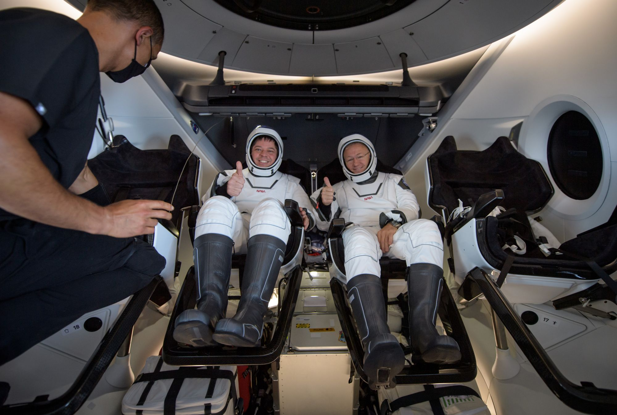NASA astronauts Robert Behnken, left, and Douglas Hurley are seen inside the SpaceX Crew Dragon Endeavour spacecraft onboard the SpaceX GO Navigator recovery ship shortly after having landed in the Gulf of Mexico off the coast of Pensacola, Florida, Sunday, Aug. 2, 2020. Photo Credit: (NASA/Bill Ingalls)