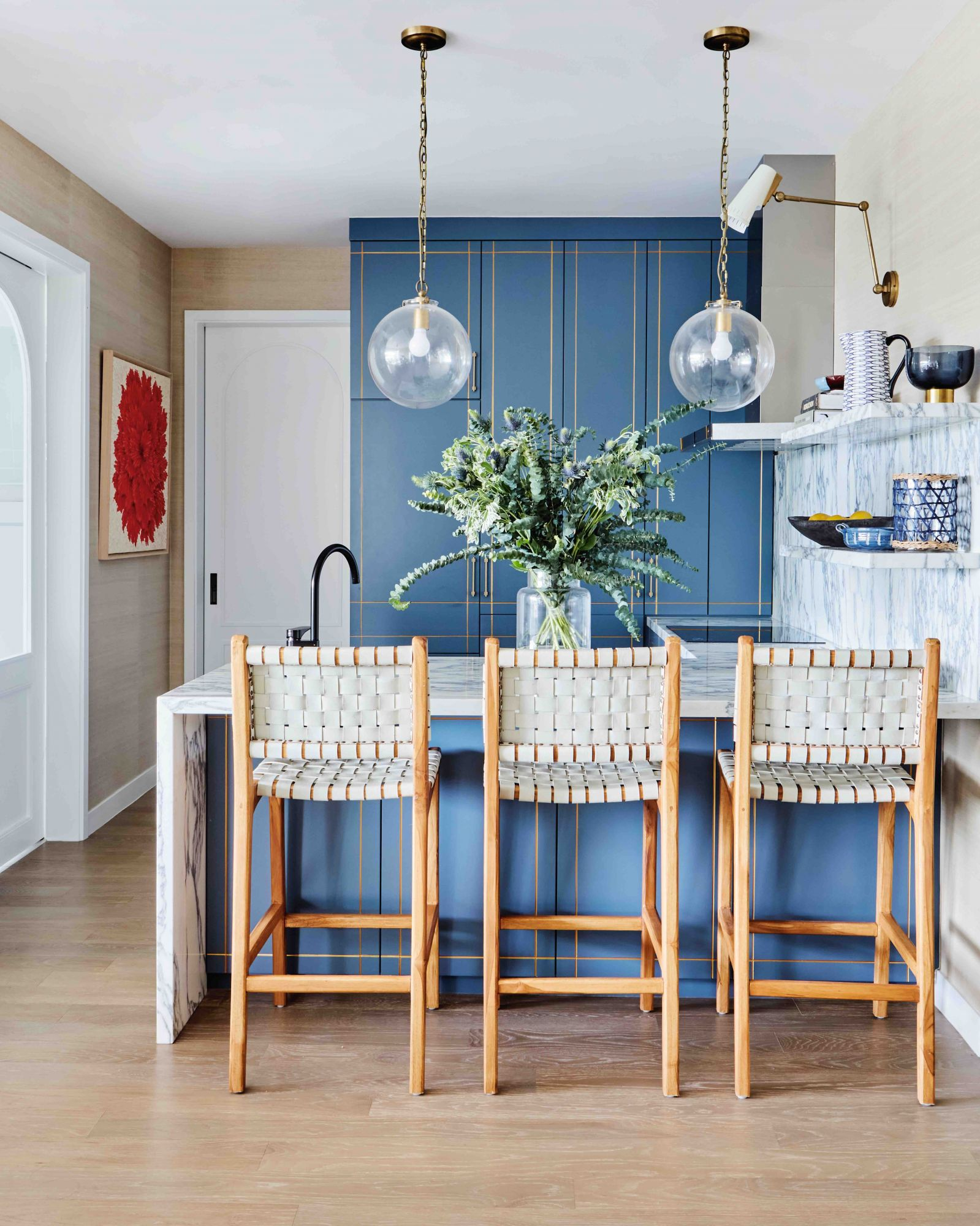 This kitchen designed by E&A Interiors combines light wood, white marble and blue cabinetry to create an elegant space