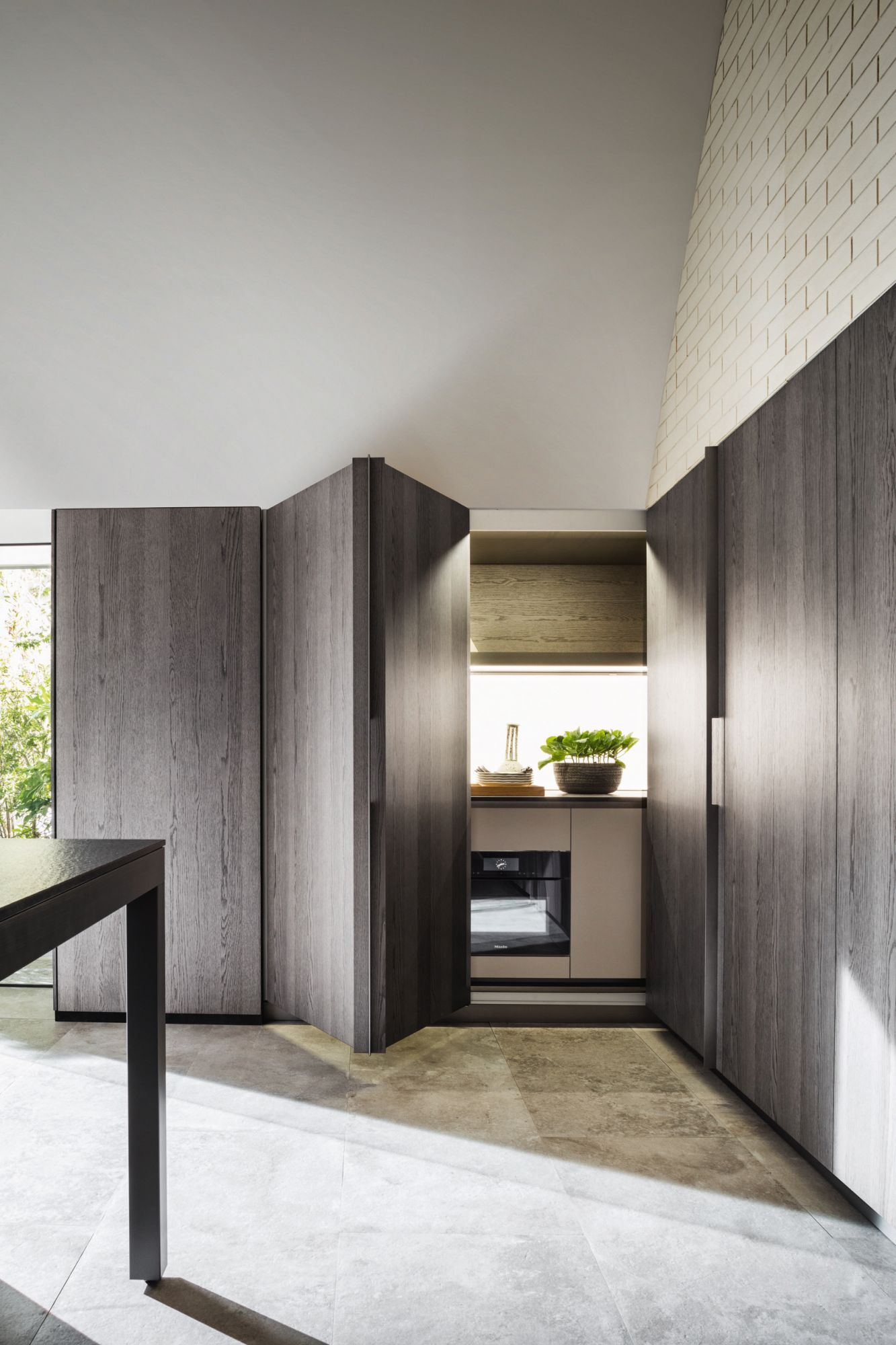 The Molteni&C | Dada Tivali kitchen system features sliding doors that can conceal the kitchen counter when it is not in use