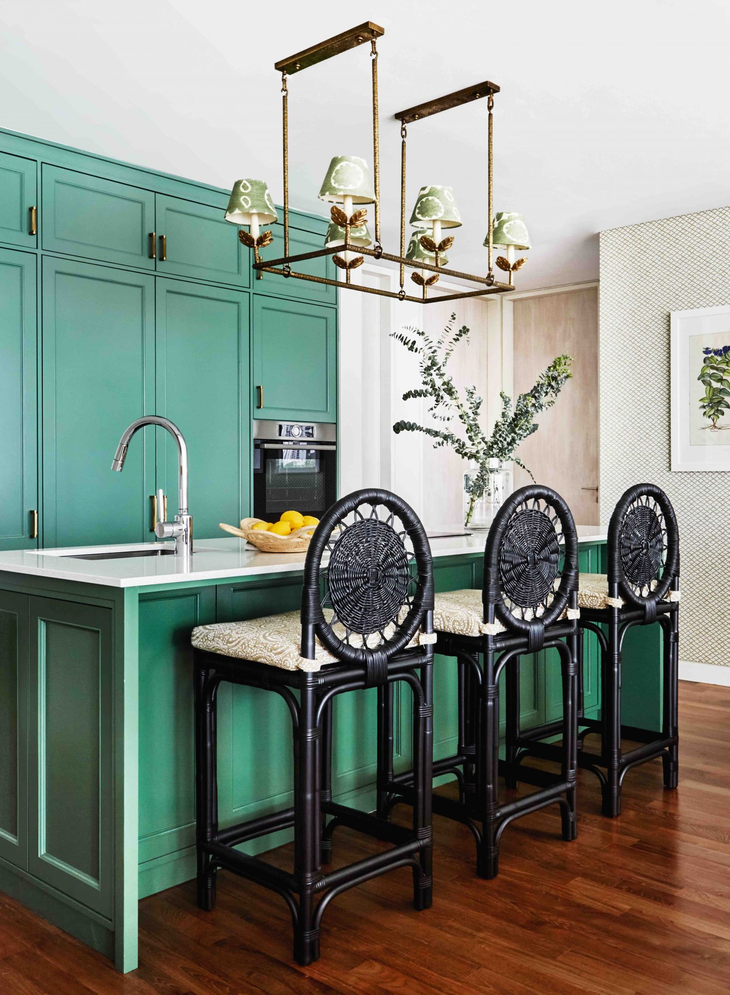 This vibrant kitchen designed by E&A Interiors employs a bold emerald hue on the cabinetry and the island