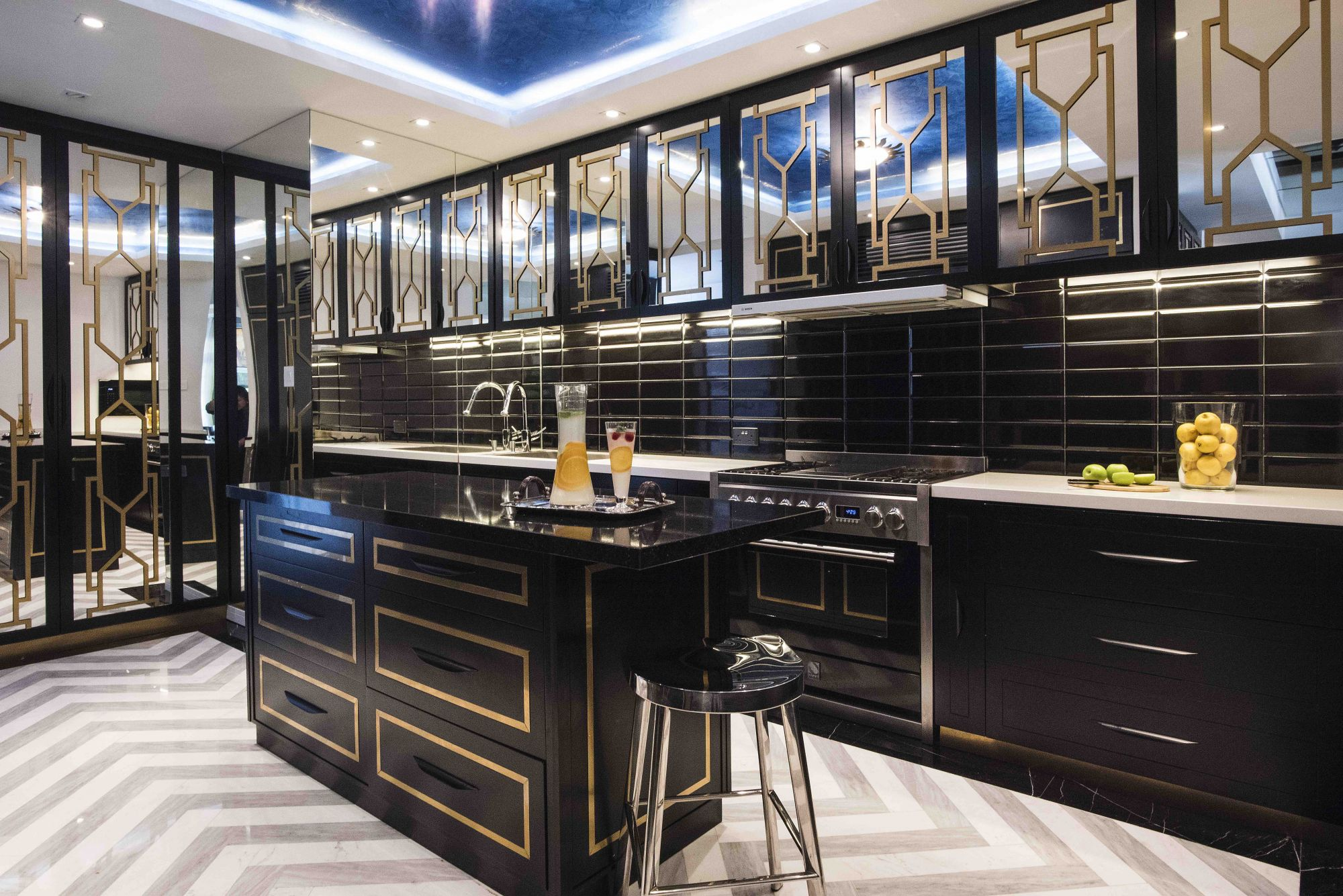 A kitchen crafted by Design Intervention, which features mirrored doors and chevron-patterned flooring