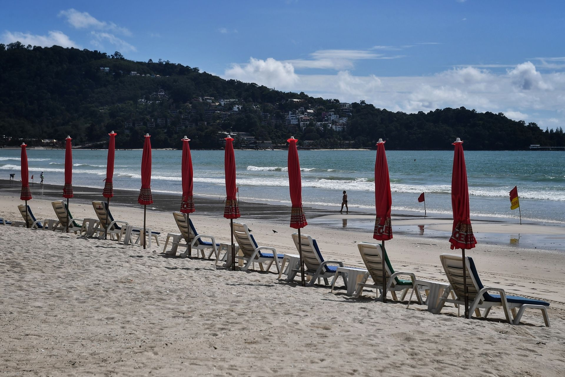 A lone tourist walks past deck chairs along an almost-empty Patong beach in Phuket on October 1, 2020, which has seen a lack of tourists due to ongoing restrictions relating to the COVID-19 novel coronavirus. (Photo by Lillian SUWANRUMPHA / AFP)