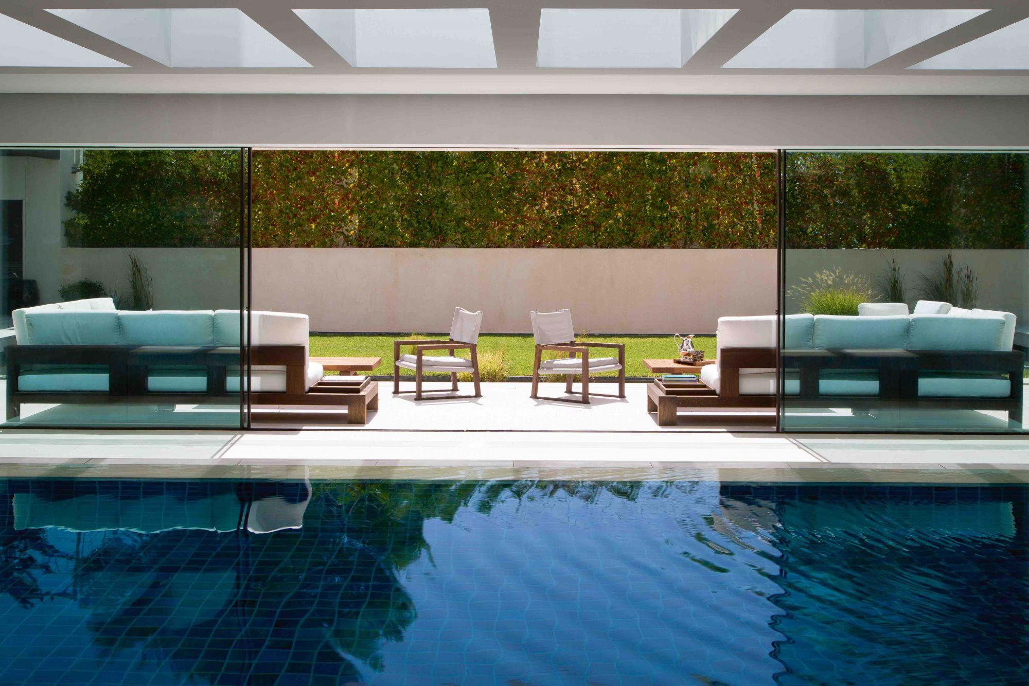 Η εσωτερική πισίνα μοιάζει με ένα συμμετρικό ζευγάρι καναπέδες και πολυθρόνες μπροστά από το γκαζόν