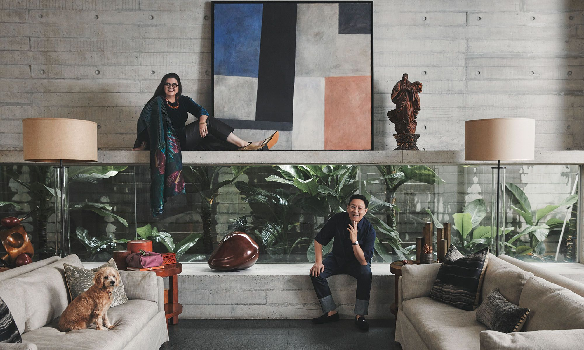 The couple and their dog Biggles in the living room, which features a long horizontal alcove with a window that perfectly frames the plants; the space is also thoughtfully decorated with seedpods and seed sculptures; Wong wears a Piaget watch.