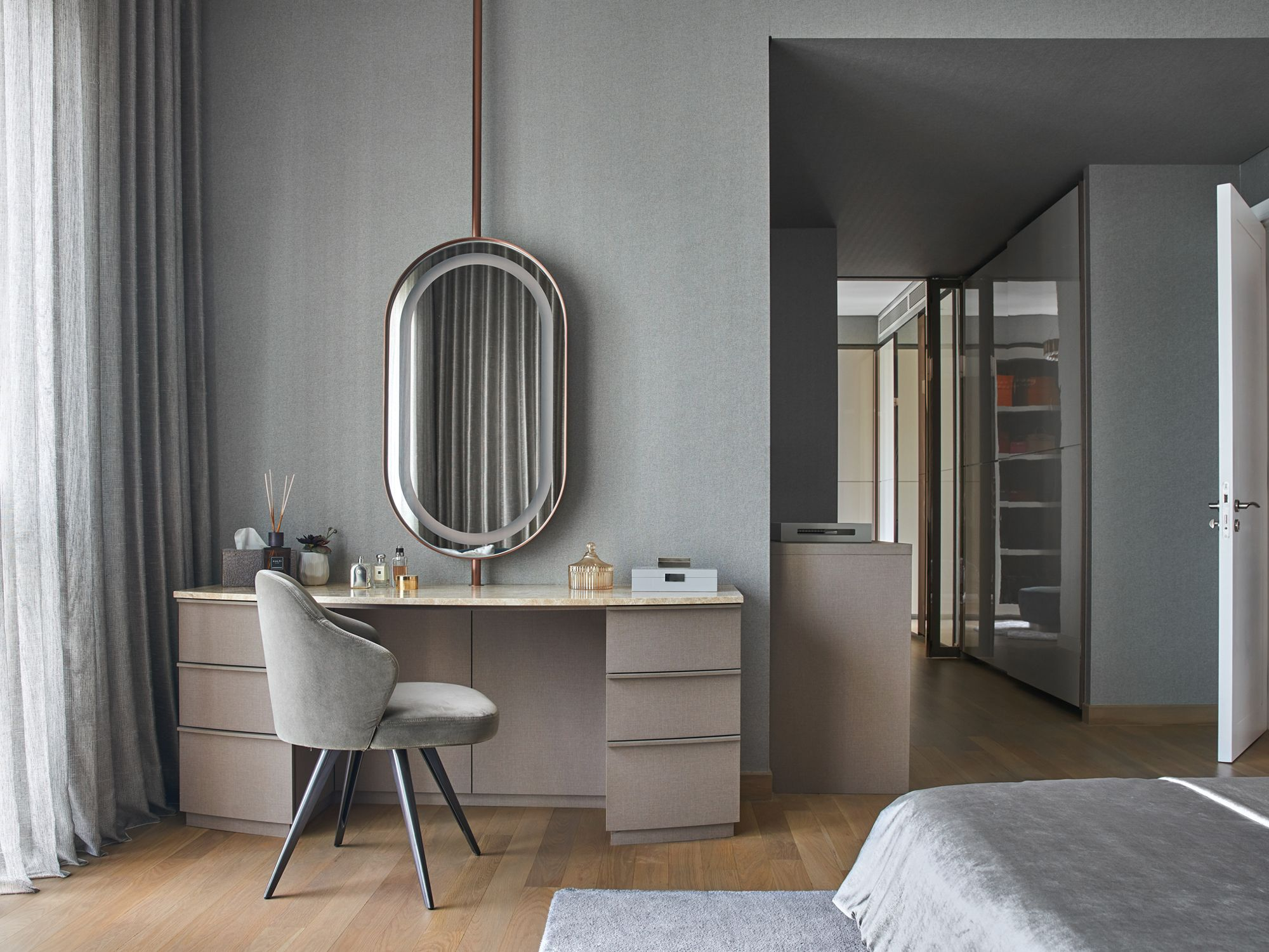 The master bedroom extends the visual language via an identical palette and a mirror similar to that in the dressing area