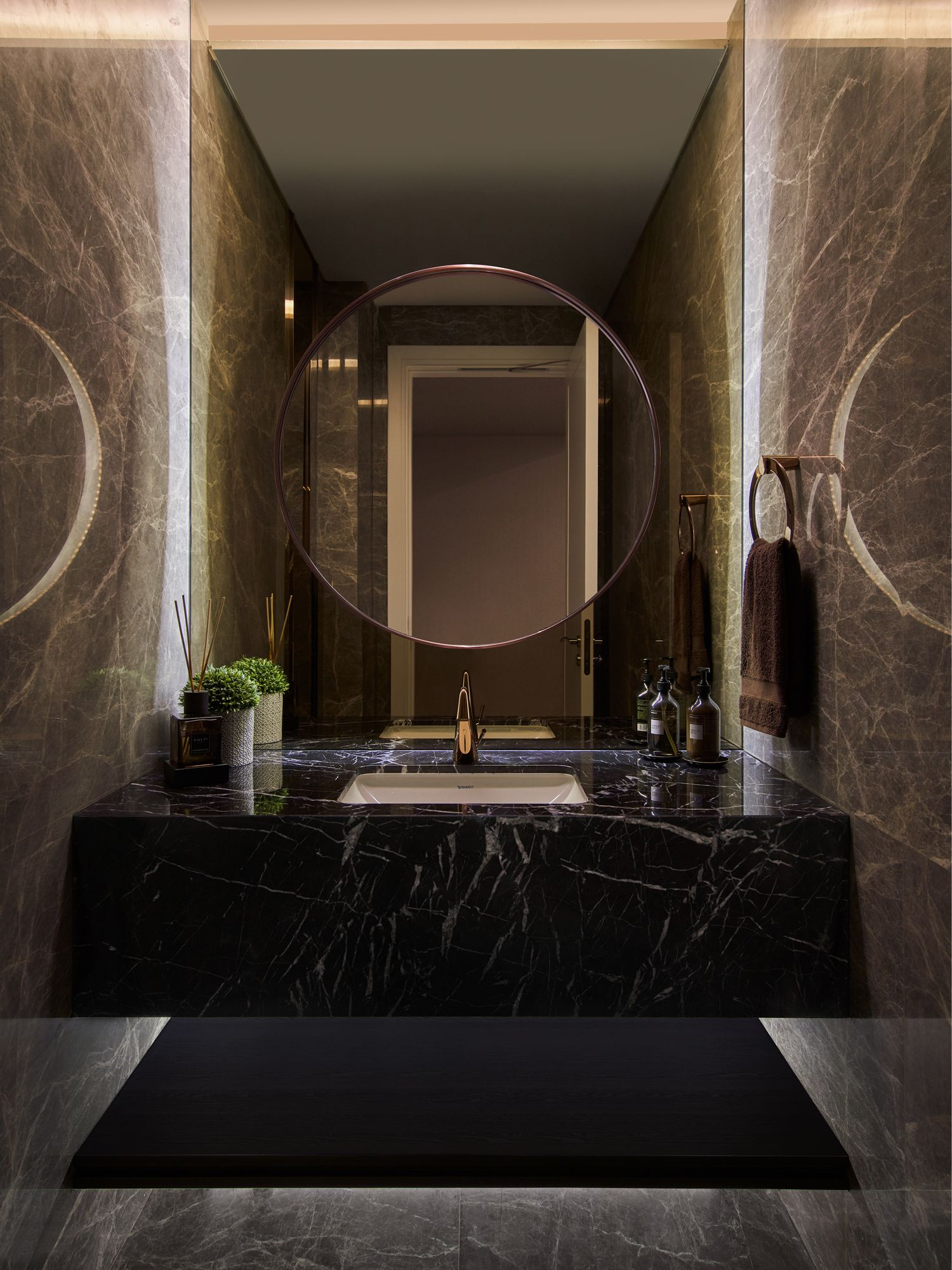 The powder room features a solid block of black marble for the basin and mirrored walls that visually expand its dimensions