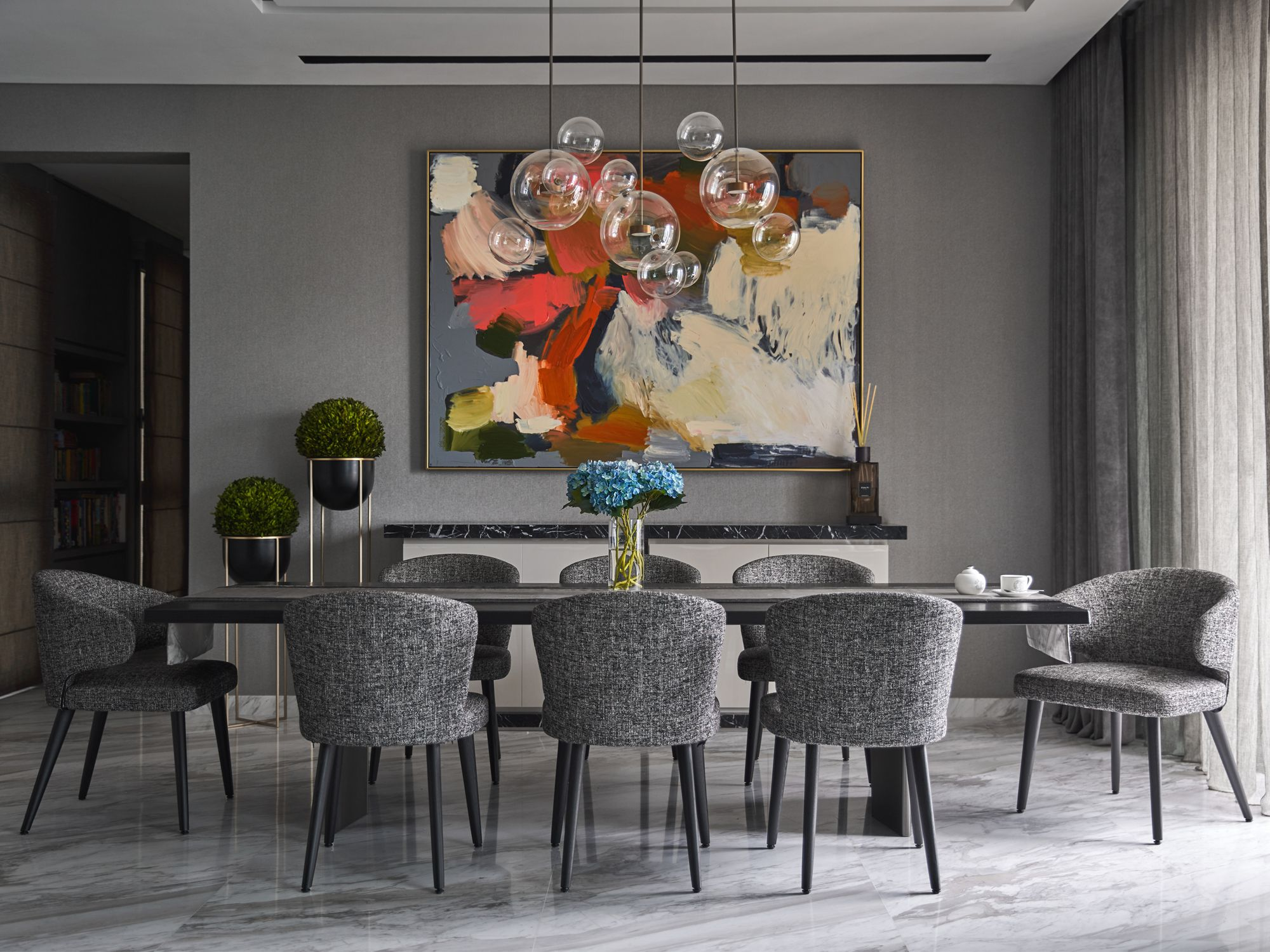 The dining area is large and spacious, featuring the complementing marble and grey combination seen throughout the apartment