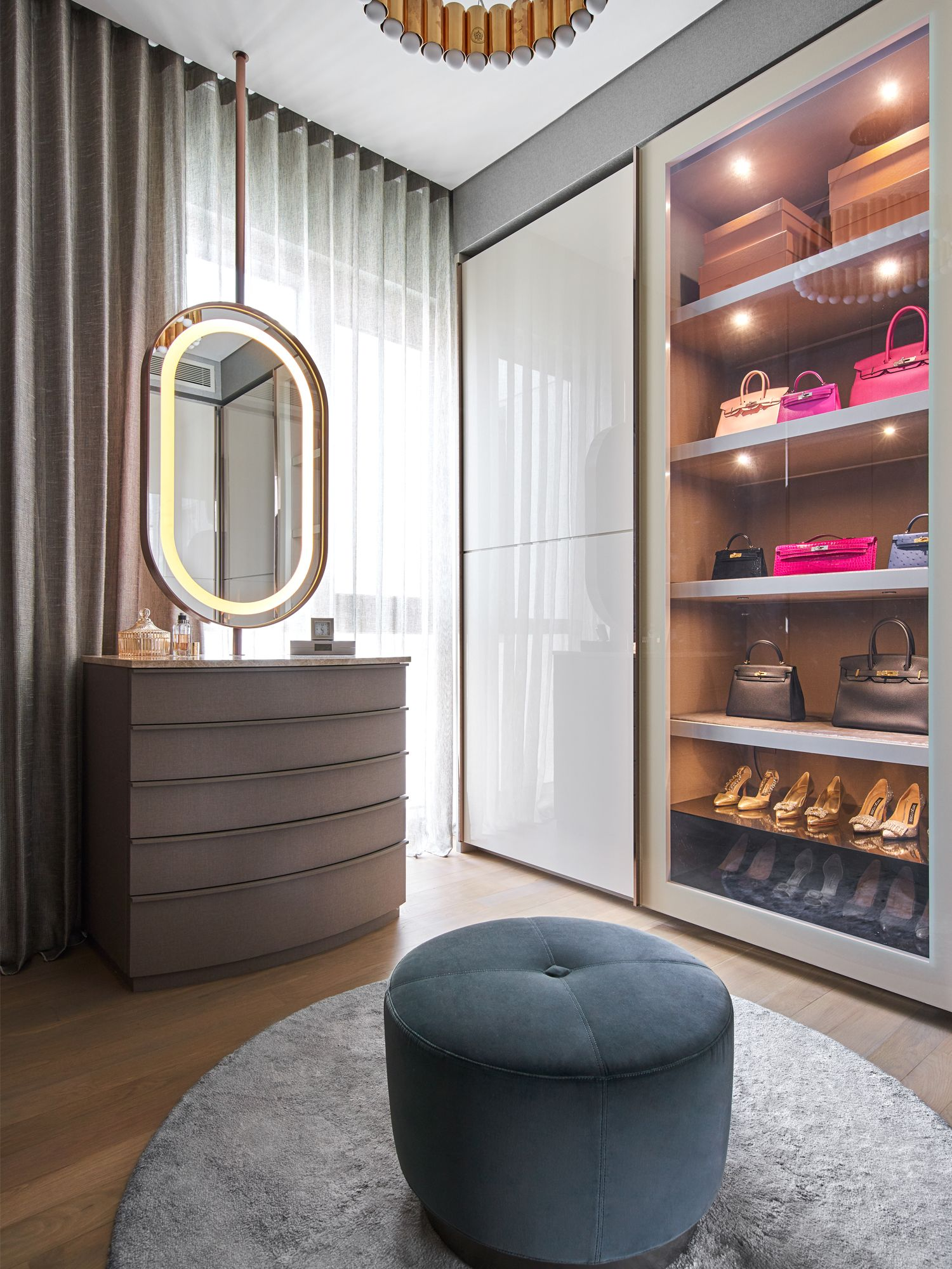 The walk-in wardrobe features cabinetry with gold trimming and built-in lighting to showcase the wife's favourite bags and shoes