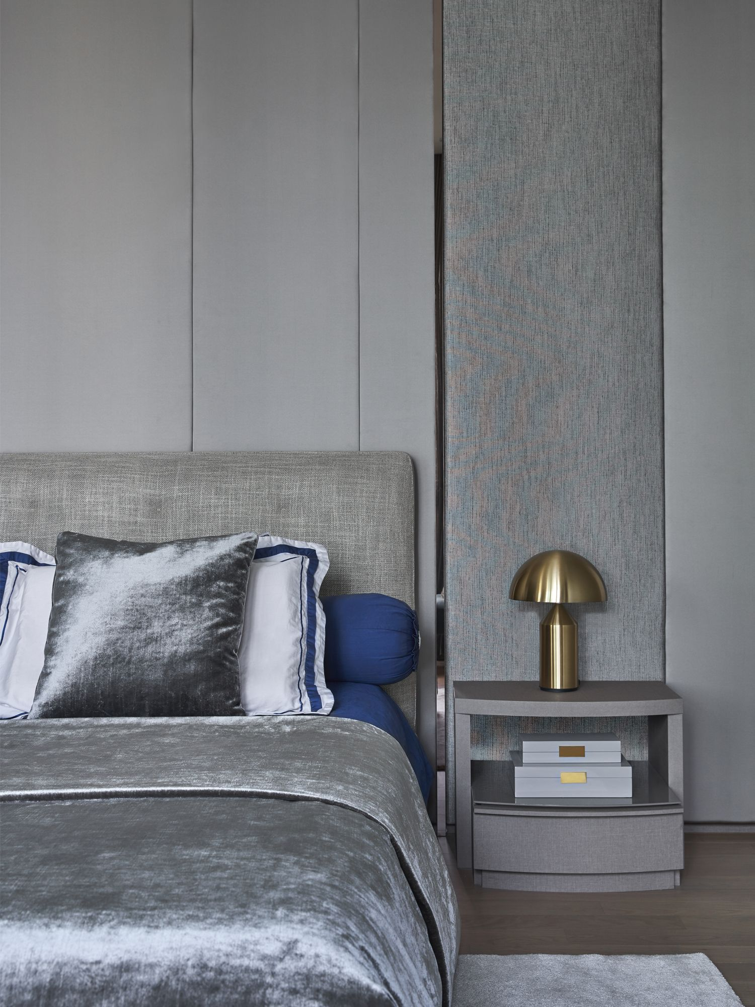 The use of upholstered panels in shades of grey and chrome accents is luxurious yet understated