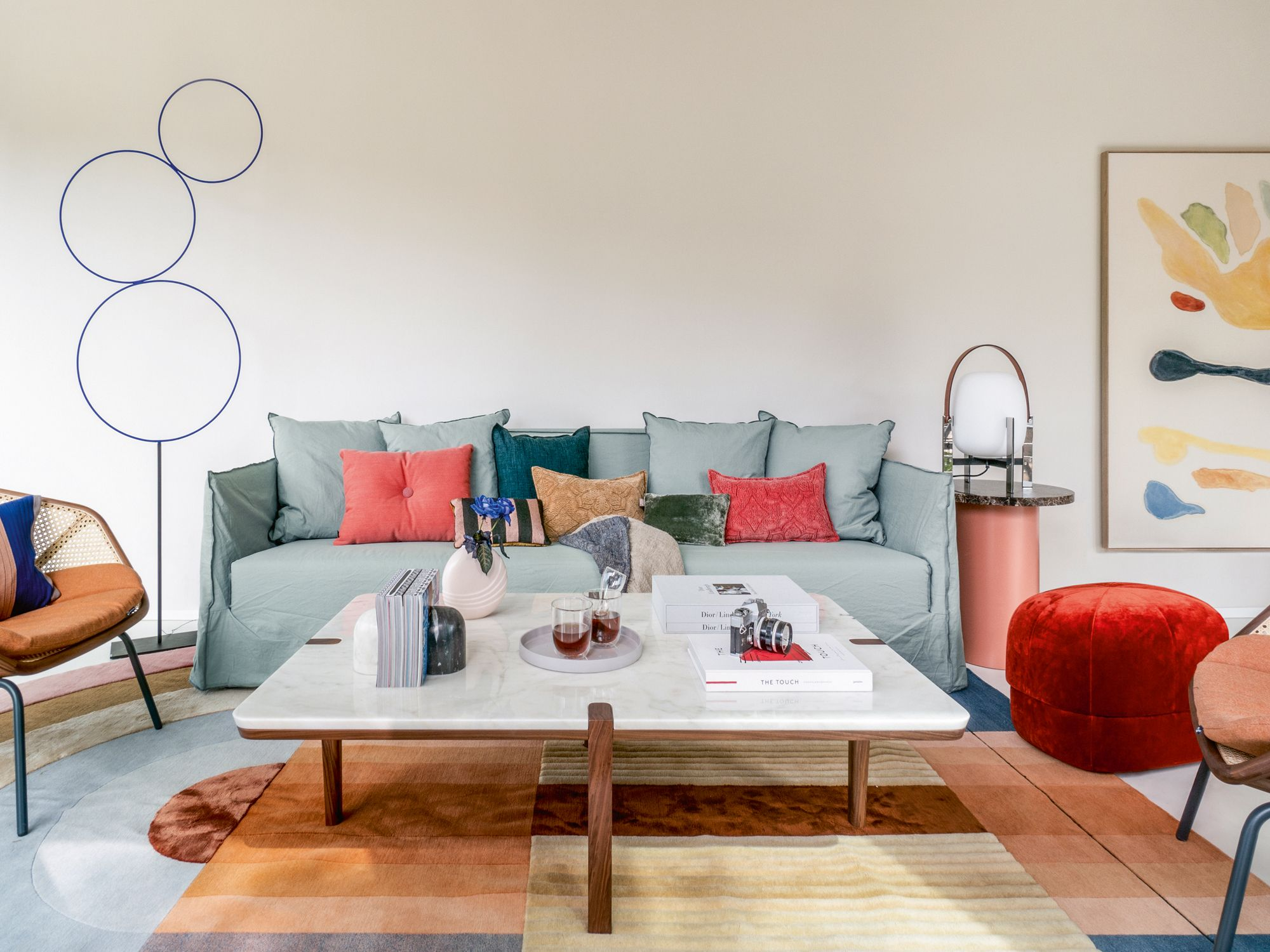 The living room is furnished with the Gervasoni Ghost sofa, Miniform armchairs, We Wood coffee table, Normann Copenhagen pouf, Santa & Cole lamp and E15 Enoki side table