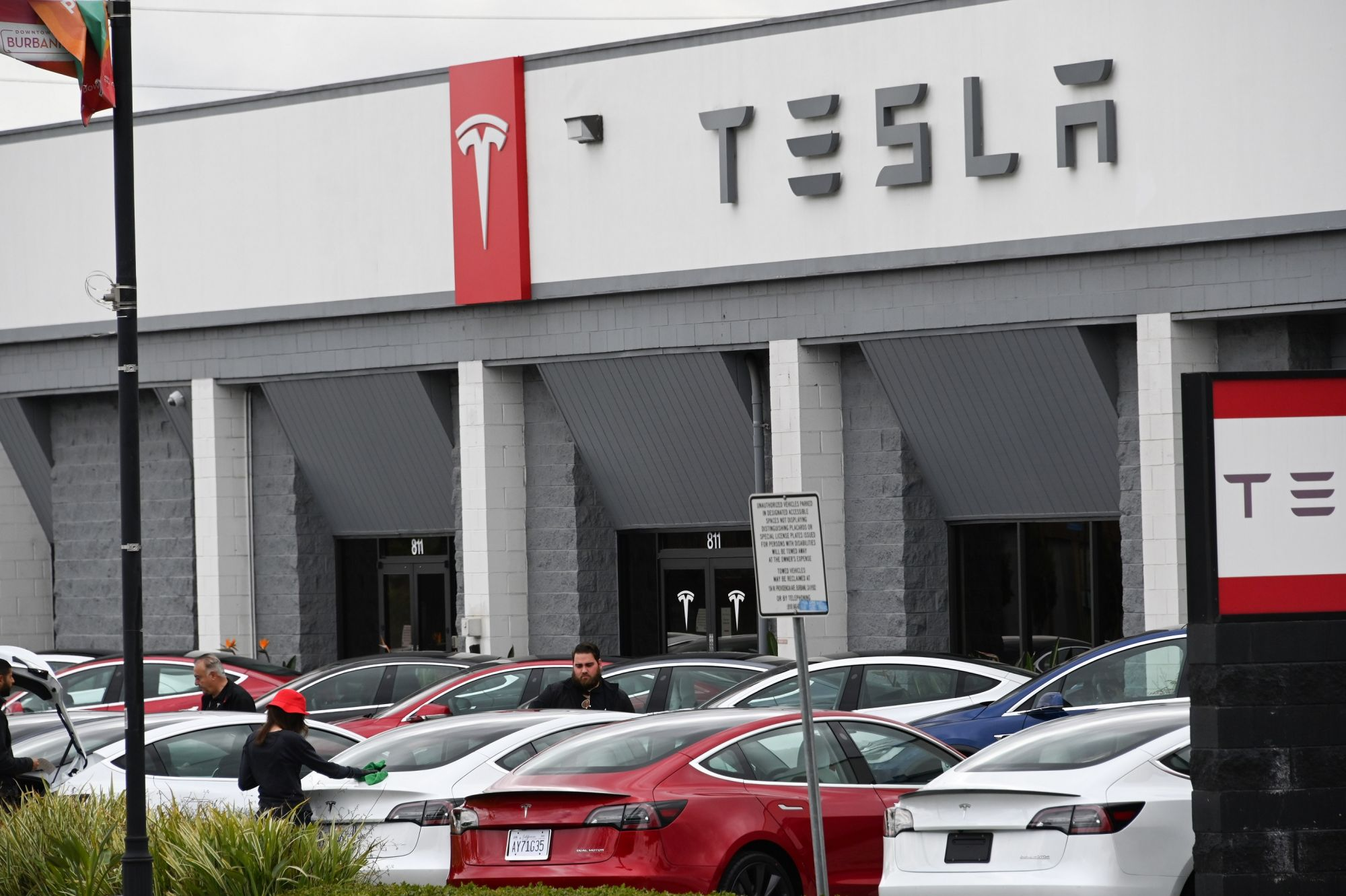 Telsa employees work outside a Tesla showroom in Burbank, California, March 24, 2020. - Luxury electric car maker Tesla ended up closing its California plant in Fremont, a concession by its maverick head Elon Musk after a drawn-out standoff with the state authorities over the spread of the virus. (Photo by Robyn Beck / AFP)