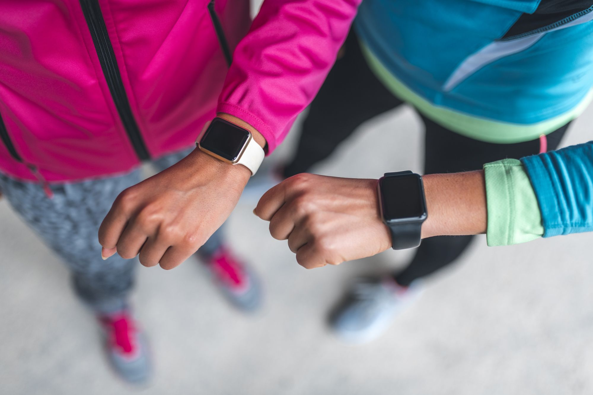 Close-up shot of two young sportswomen checking pulse on smart watch.
