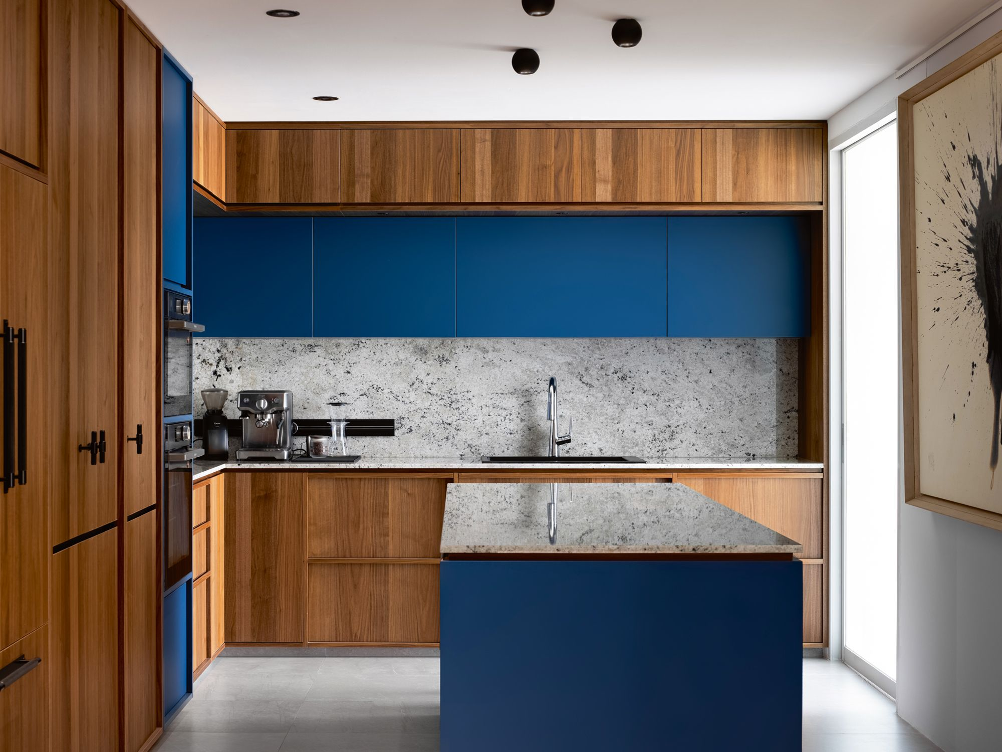 Blue cabinetry and the rugged texture of the backsplash make the kitchen pop