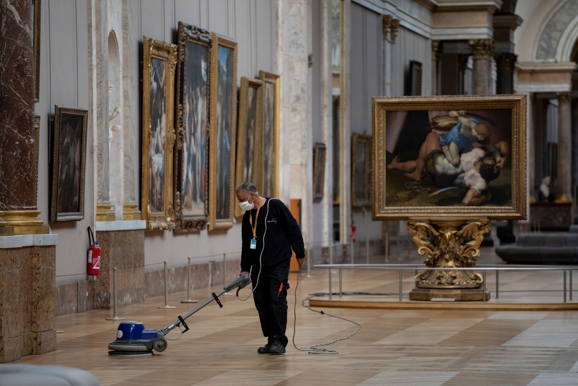 """A picture taken on June 23, 2020 shows an employee cleaning the floor of a room of the Musee du Louvre in Paris. - The Louvre museum will reopen its doors on July 6, 2020, after months of closure due to lockdown measures linked to the COVID-19 pandemic, caused by the novel coronavirus. The coronavirus crisis has already caused """"more than 40 million euros in losses"""" at the Louvre, announced its president and director Jean-Luc Martinez, who advocates a revival through """"cultural democratization"""" and is prepari"""