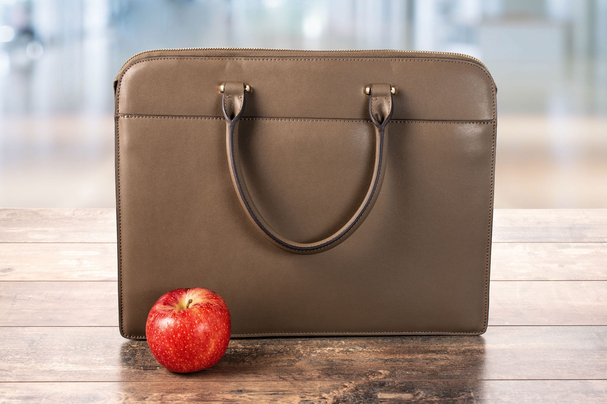 business bag, briefcase and red apple on a wooden table on a blurry background. proper nutrition at work in the office. Diet And healthy Food in the office; Shutterstock ID 1856322349; Purchase Order: ETX/Relaxnews/Fil; Client/Licensee: Arnaud POURPOINT