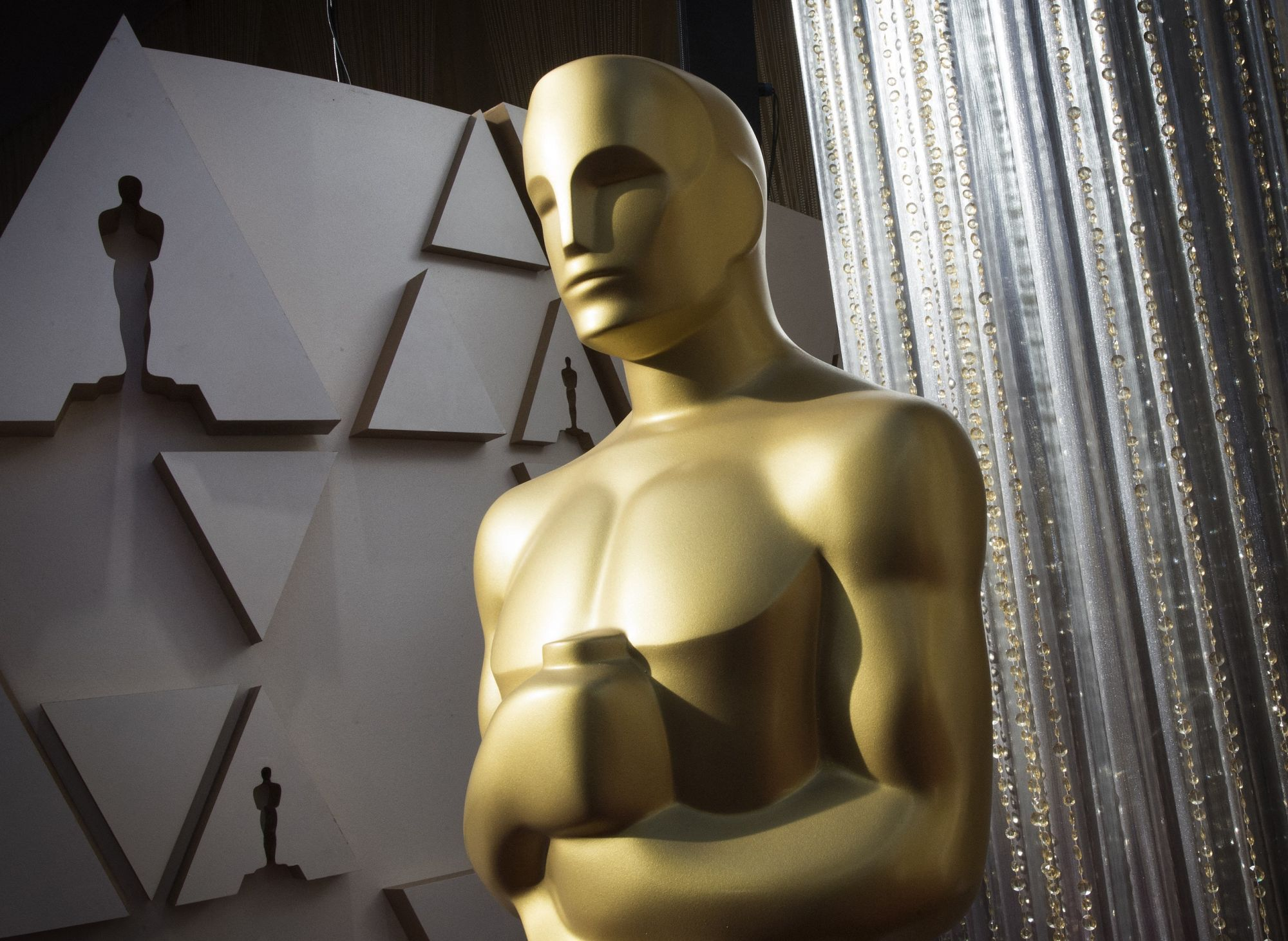 """(FILES) In this file photo an Oscars statue is displayed on the red carpet area on the eve of the 92nd Oscars ceremony at the Dolby Theatre in Hollywood, California, on February 8, 2020. - This year's Oscars will be broadcast live and """"in-person"""" from multiple locations, the Academy said on February 10, 2021, as details of Hollywood's pandemic-delayed big night finally begin to take shape. The Academy Awards in recent decades have taken place at the Dolby Theatre in Los Angeles, but with the United States'"""