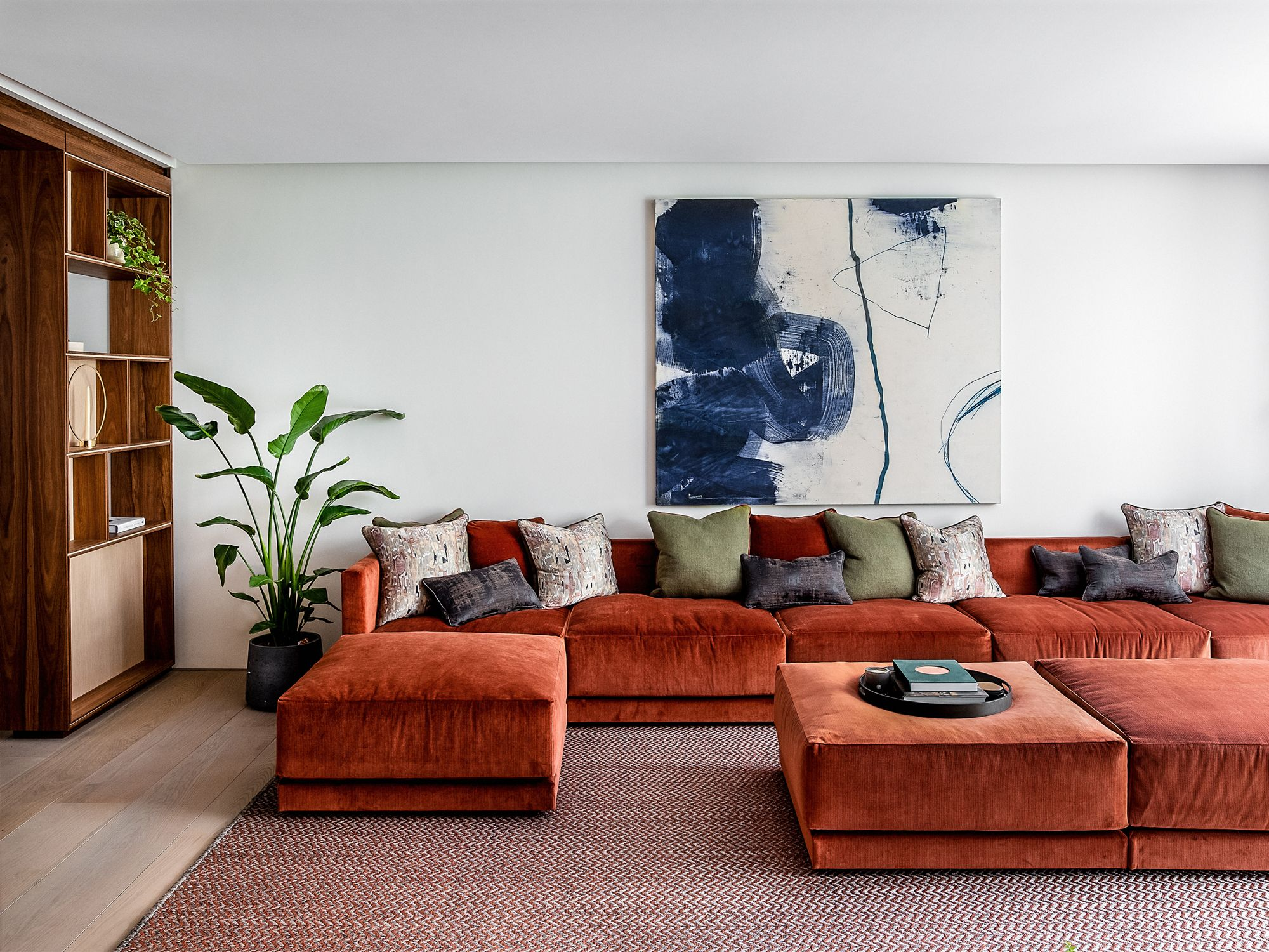 An autumnal colour palette dominates the main living room, where a large sofa designed by Echlin takes focal point