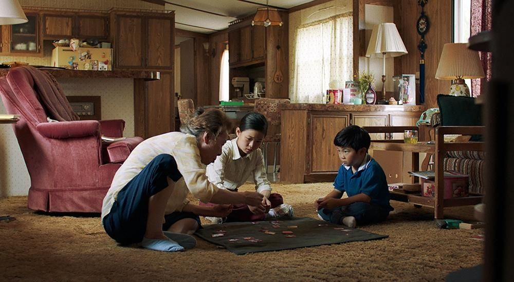 Soon-ja (Youn Yuh-jung) teaching her grandchildren Go-Stop, a traditional Korean card game. The living room is a prominent feature in the film (Image: IMDB, Courtesy of A24)
