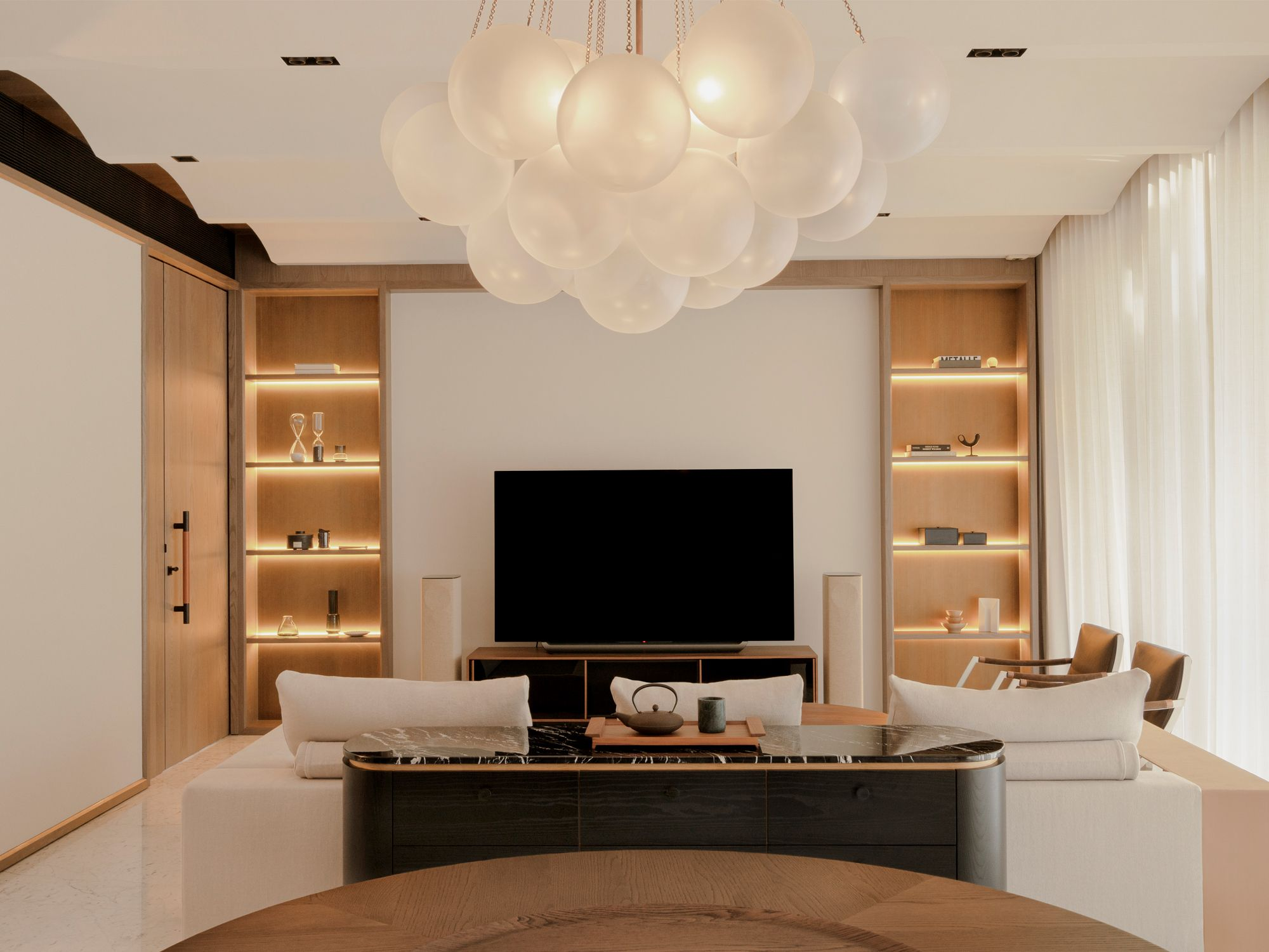 The backlit shelves in the living room showcase objets d'art and collectibles
