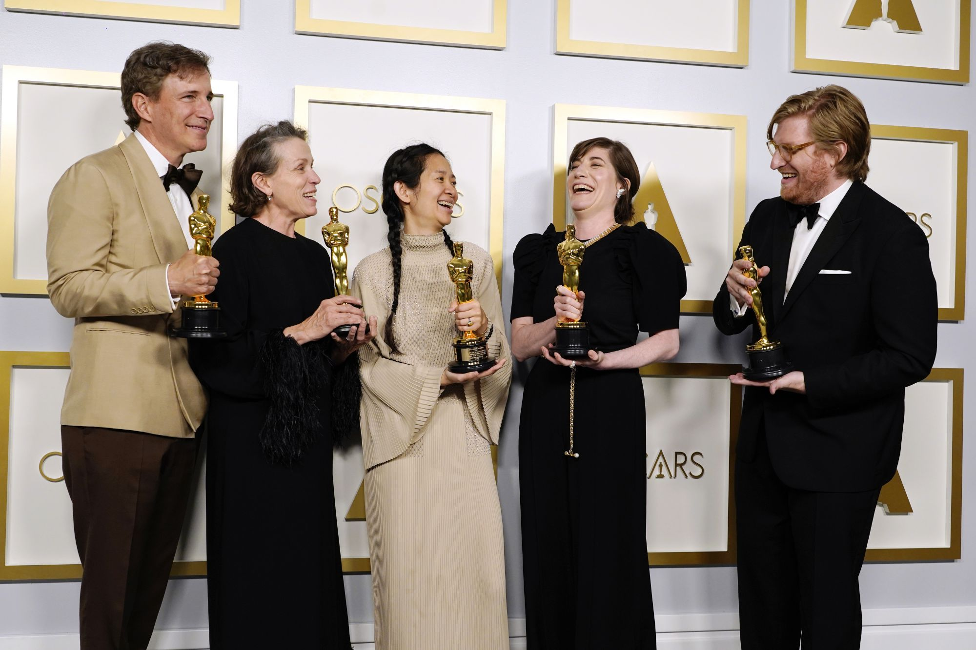 """LOS ANGELES, CALIFORNIA - APRIL 25: (L-R) Peter Spears, Frances McDormand, Chloe Zhao, Mollye Asher, and Dan Janvey, winners of Best Picture for """"Nomadland,"""" pose in the press room at the Oscars on Sunday, April 25, 2021, at Union Station in Los Angeles. (Photo by Chris Pizzello-Pool/Getty Images)"""